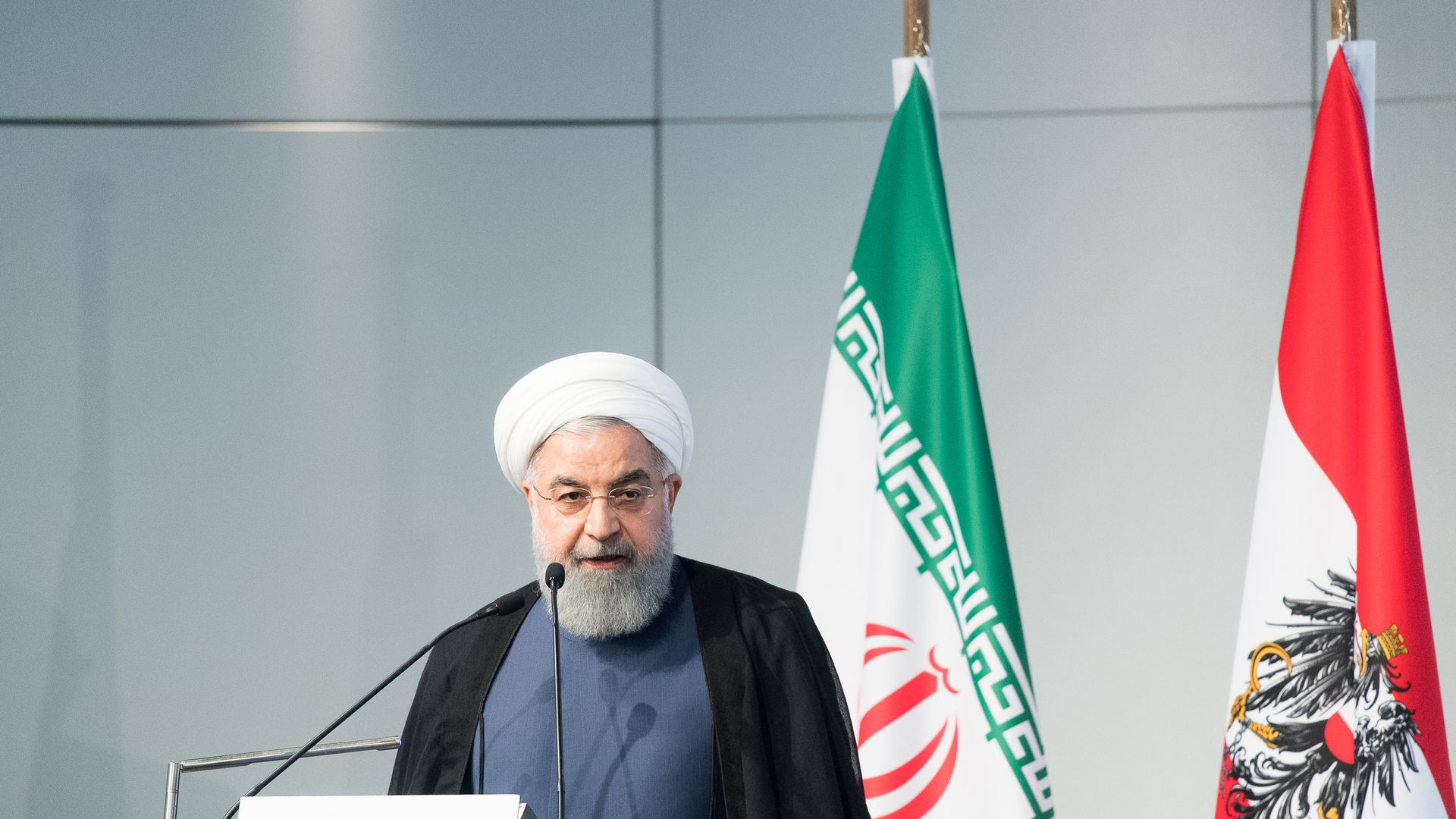 Iranian President Hassan Rouhani speaking in front of two flags.