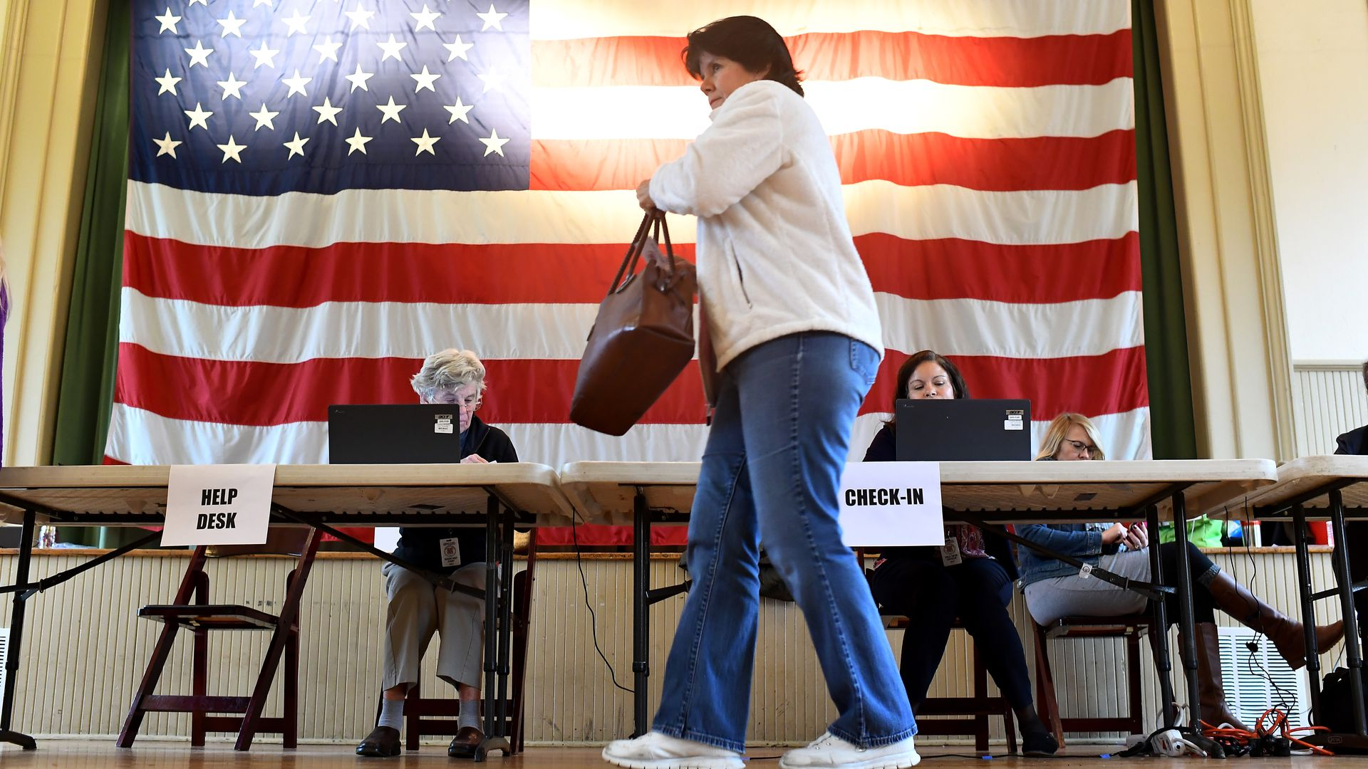 A woman votes in Virginia, with a large American flag lit up behind her as she walks.