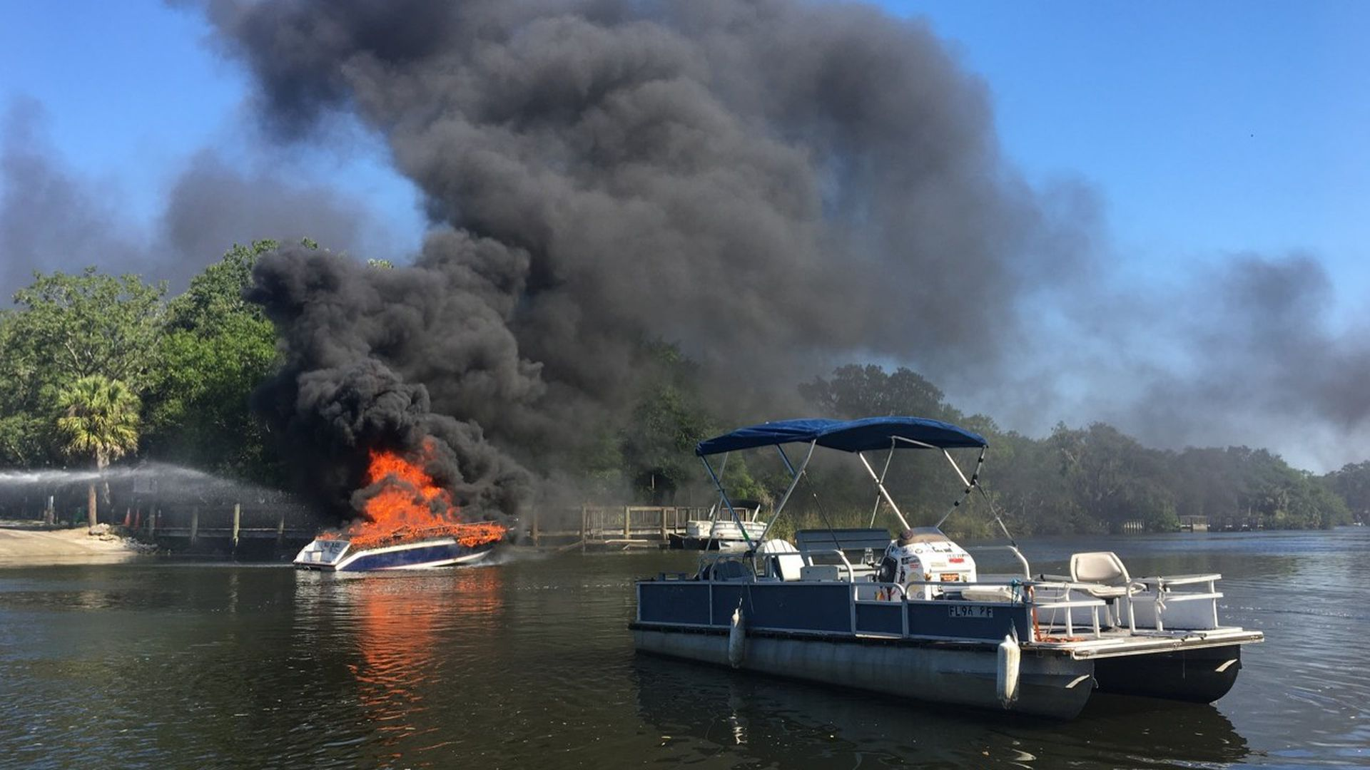 A boat up in flames on the water, with black smoke billowing overhead and another boat nearby