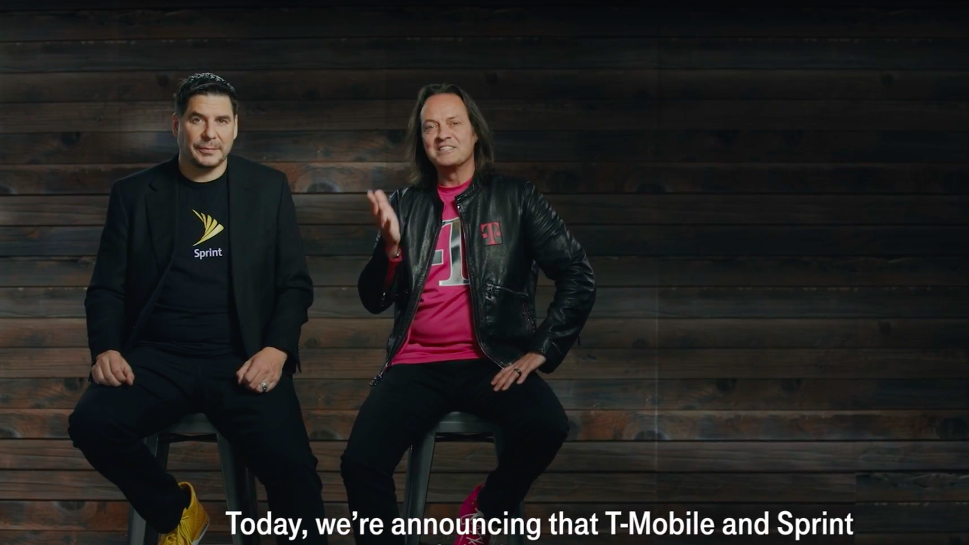 Sprint CEO Marcelo Claure and T-Mobile chief executive John Legere sit on high stools