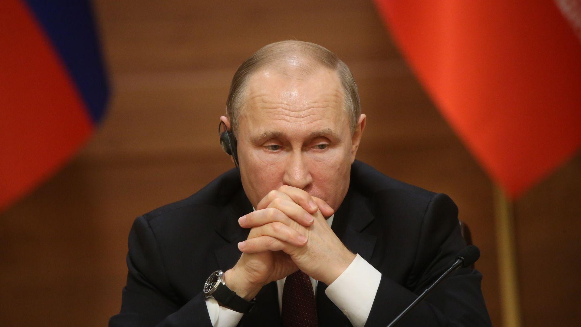 Vladimir Putin rests his head on steepled hands.