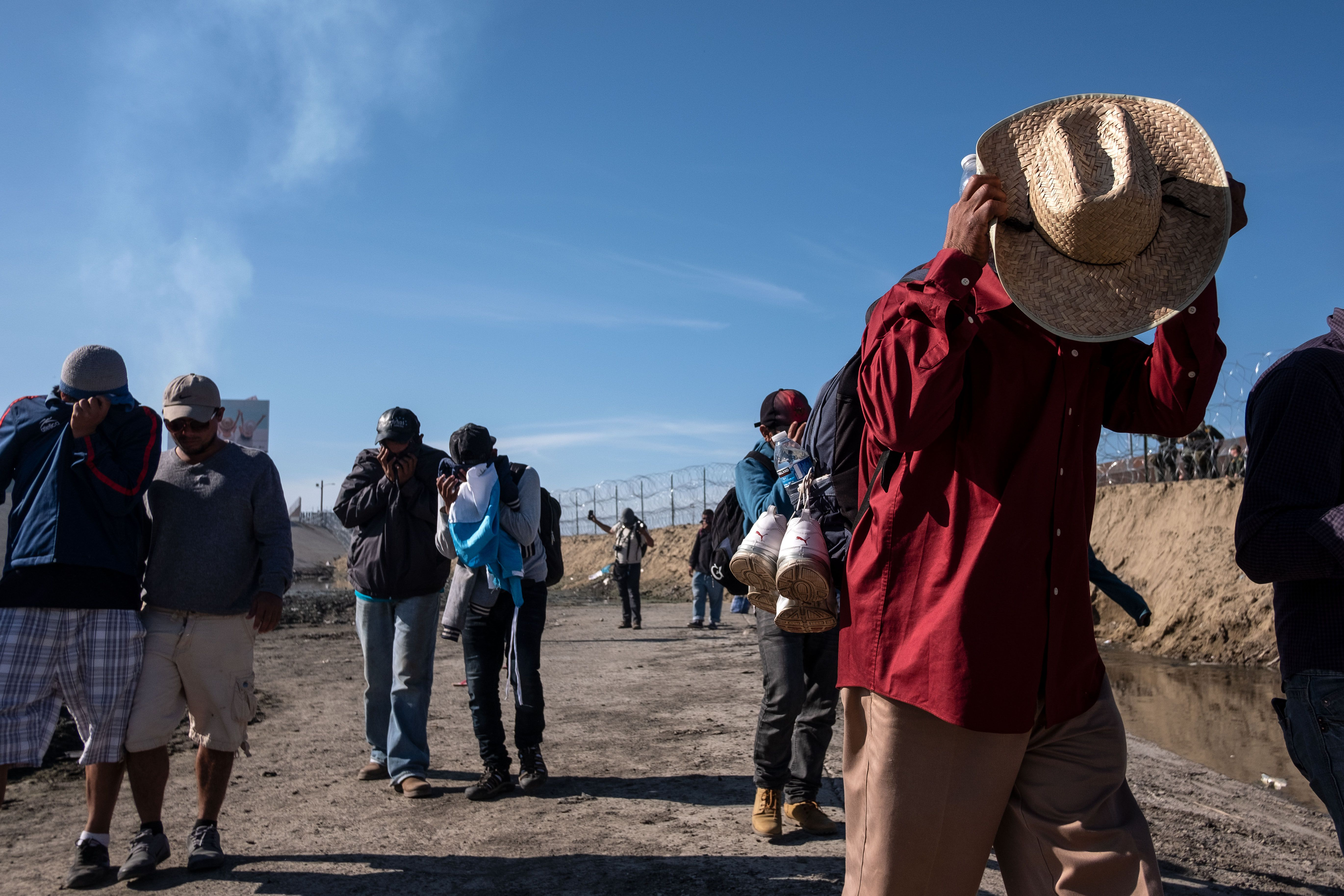 Migrants fleeing from tear gas and covering their heads and faces.