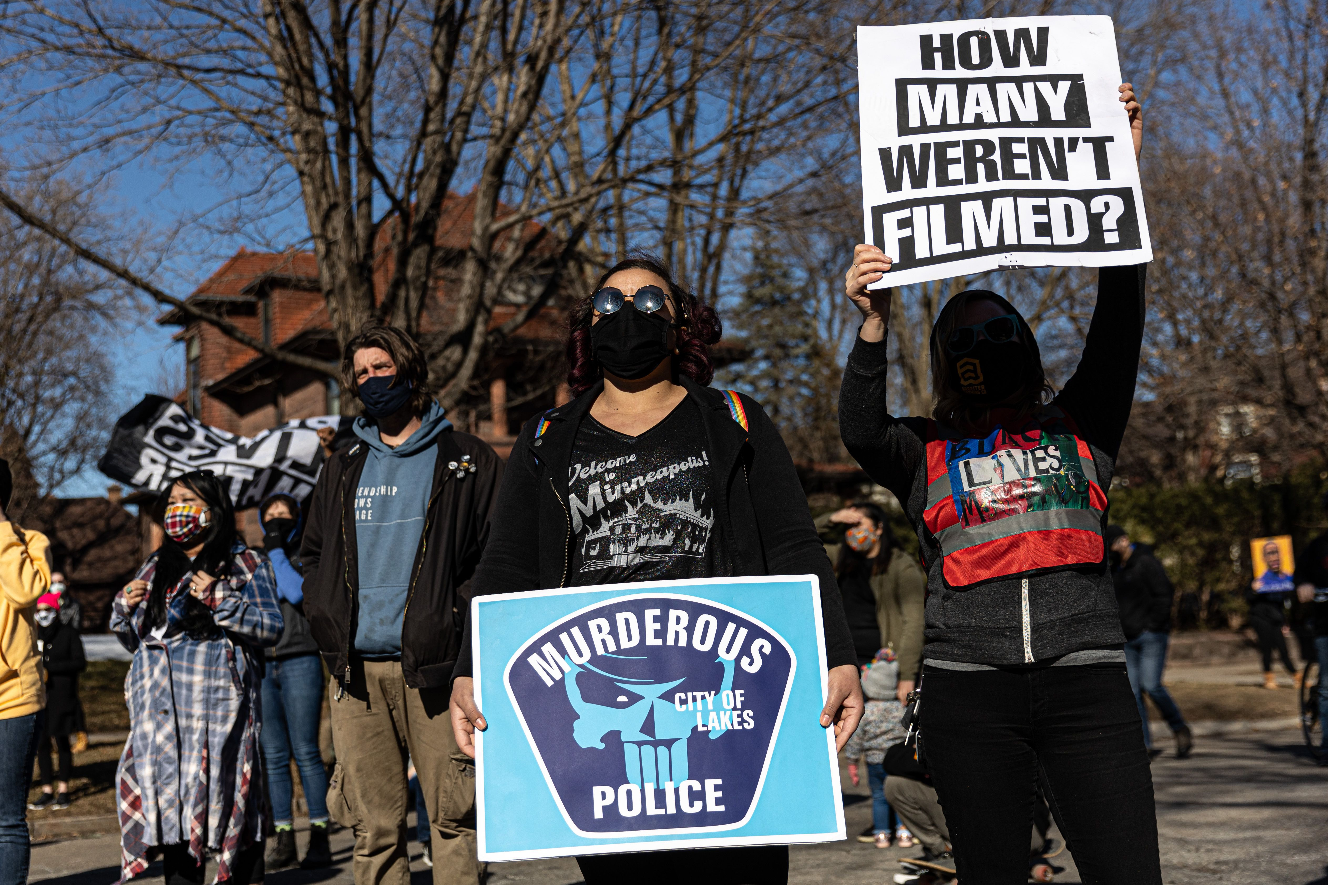 Demonstrators march while holding placards during the protest for George Floyd in St.Paul, Minnesota, on March 6