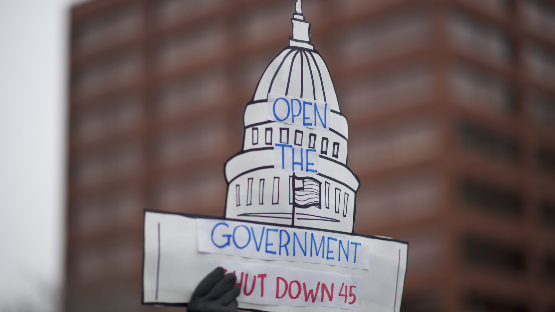 Protestor holds up sign urging Donald Trump to end shutdown