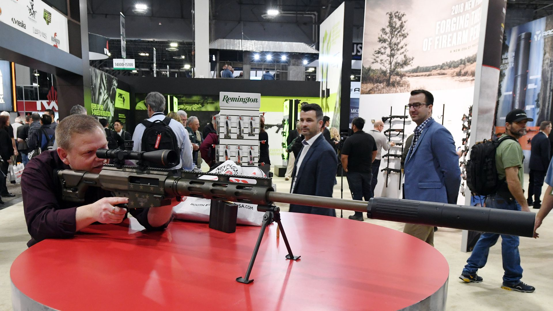 Man examines rifle at tradeshow.
