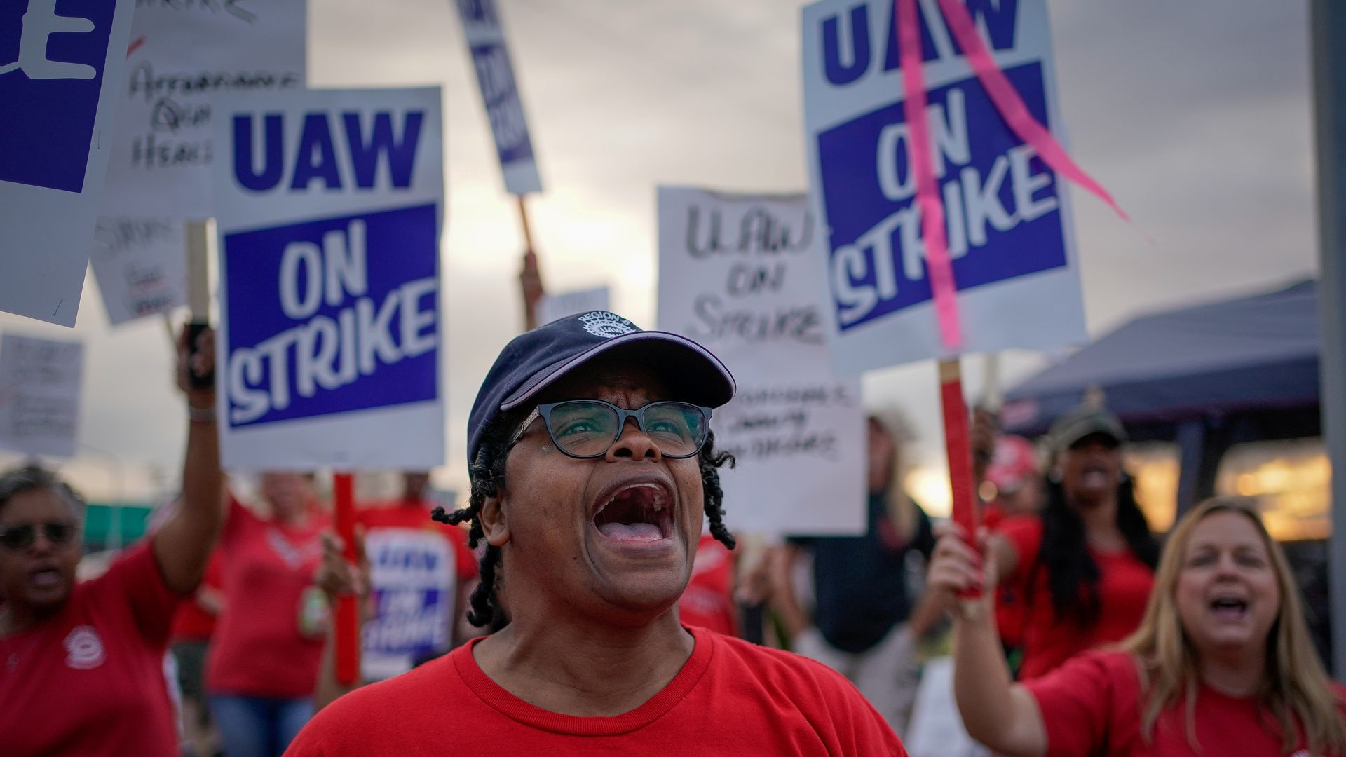 "In this image, a woman shouts while standing in front of people holding signs that say ""UAW strike"""