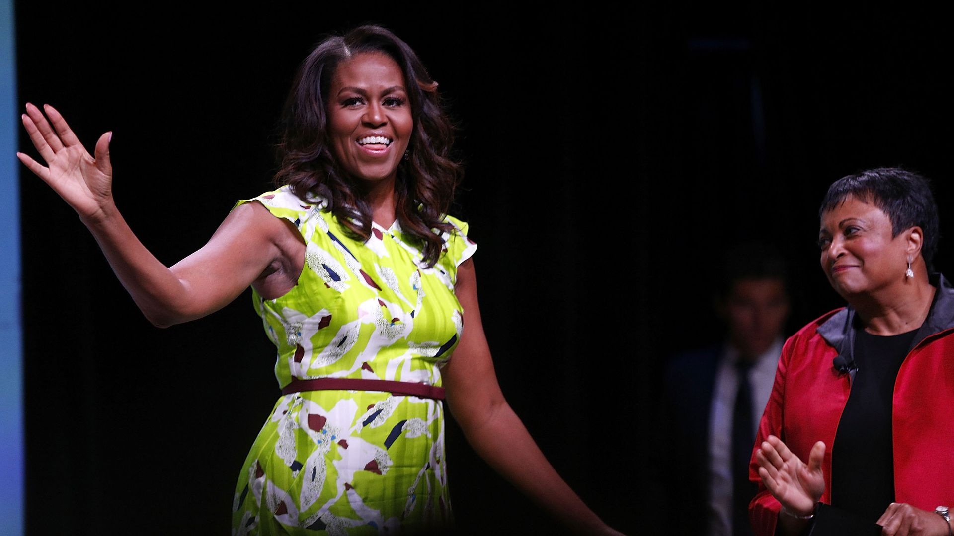 Michelle Obama waving on stage in a green flower=print dress.