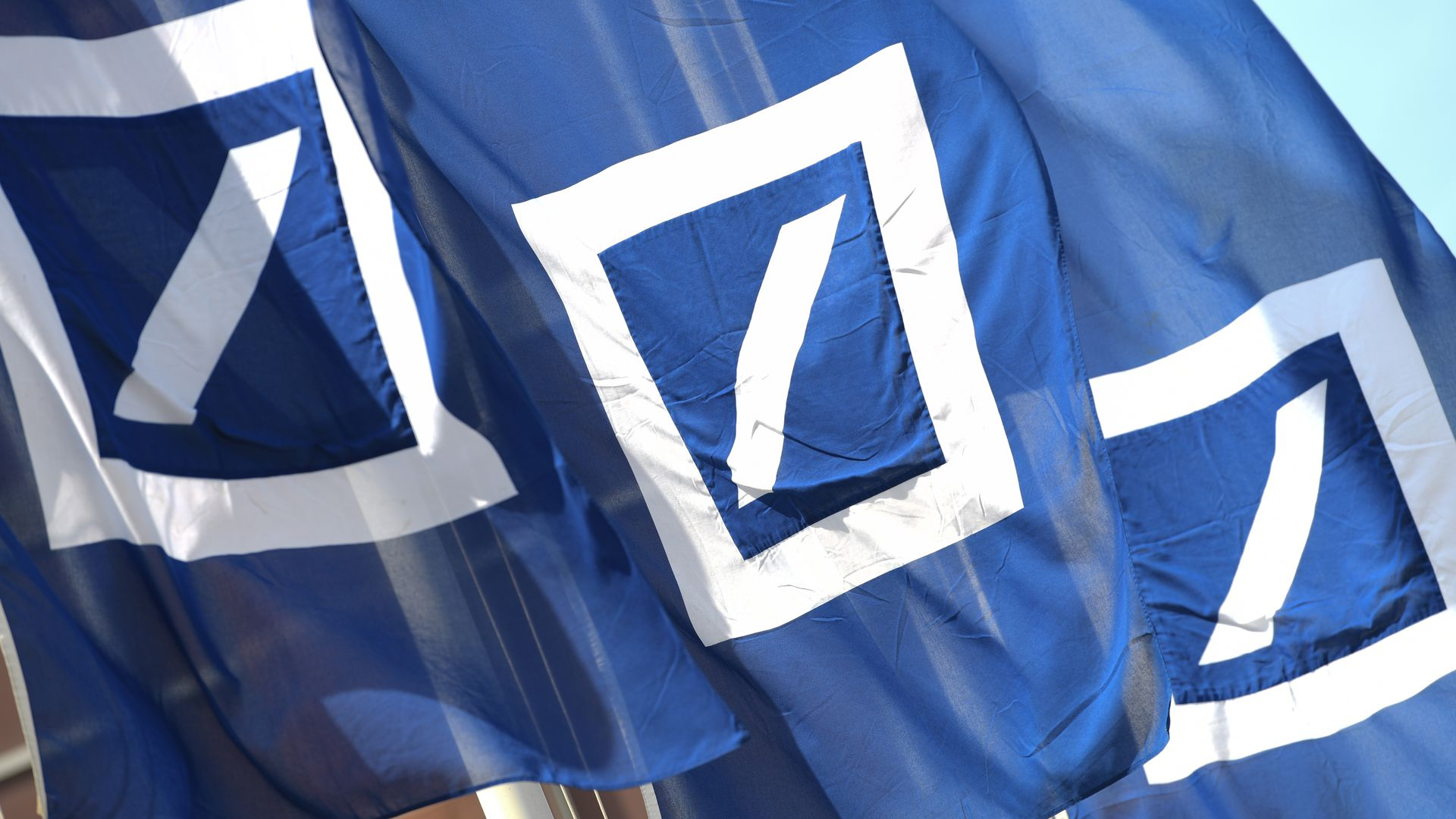 Deutsche Bank flags fly outside the bank's annual meeting.