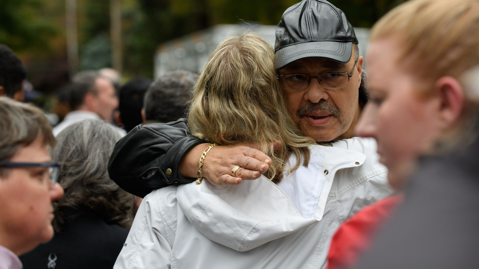 Man and woman hugging each other whlie at the crime scene of the pittsburgh shooting