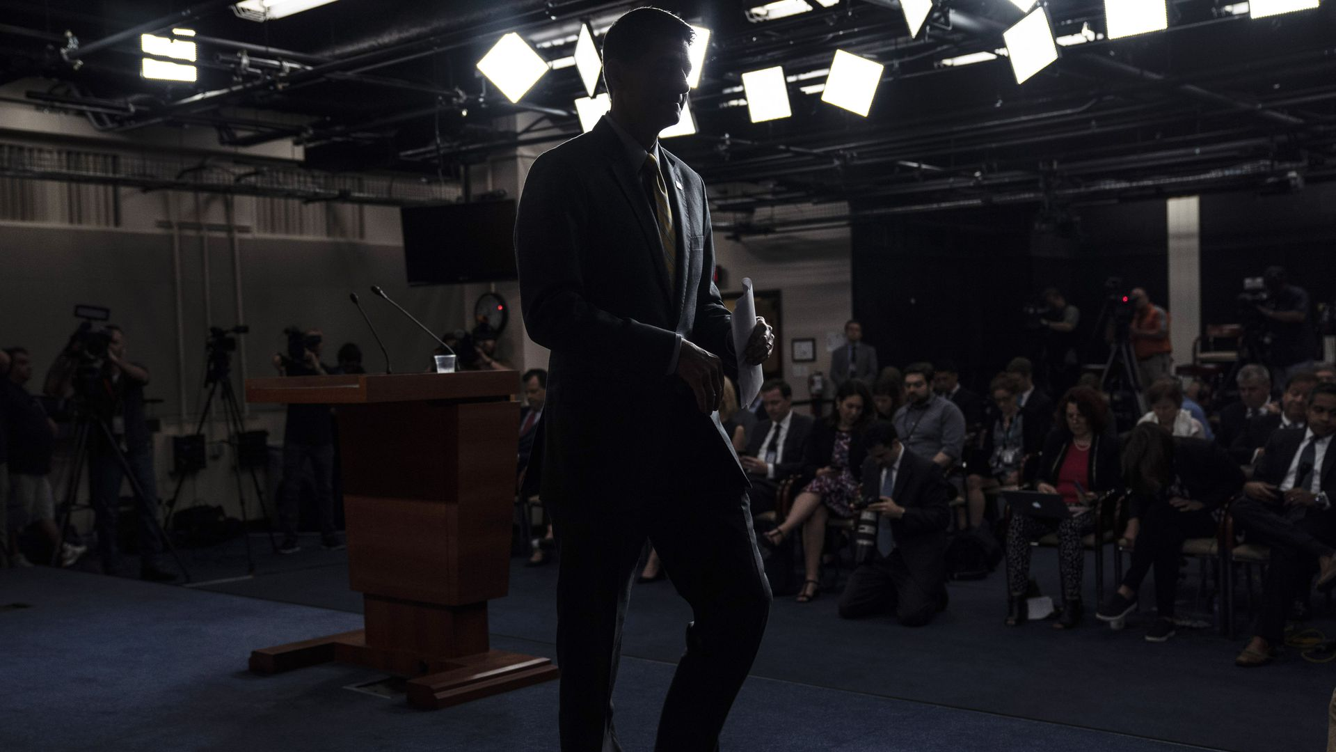 The darkened outline of Paul Ryan walking away from the podium where he spoke to reporters