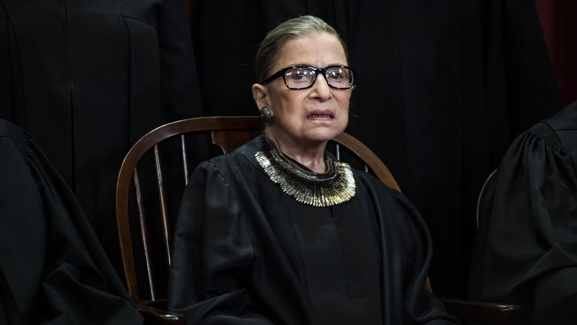 In this image, Justice Ruth Bader Ginsburg sits in a chair.