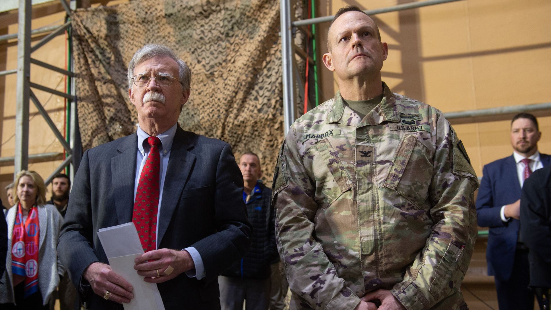 US National Security Adviser John Bolton listens as US President Donald Trump speaks to members of the US military during an unannounced trip to Al Asad Air Base in Iraq