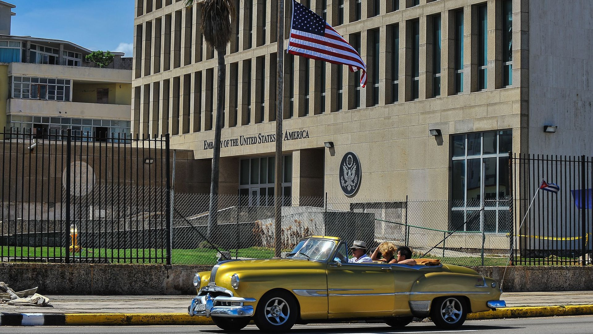 A classic car drives past the U.S. Embassy in Havana