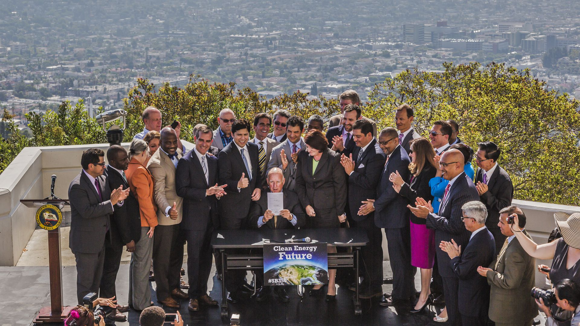 California governor Jerry Brown signs a bill into law with LA skyline behind him