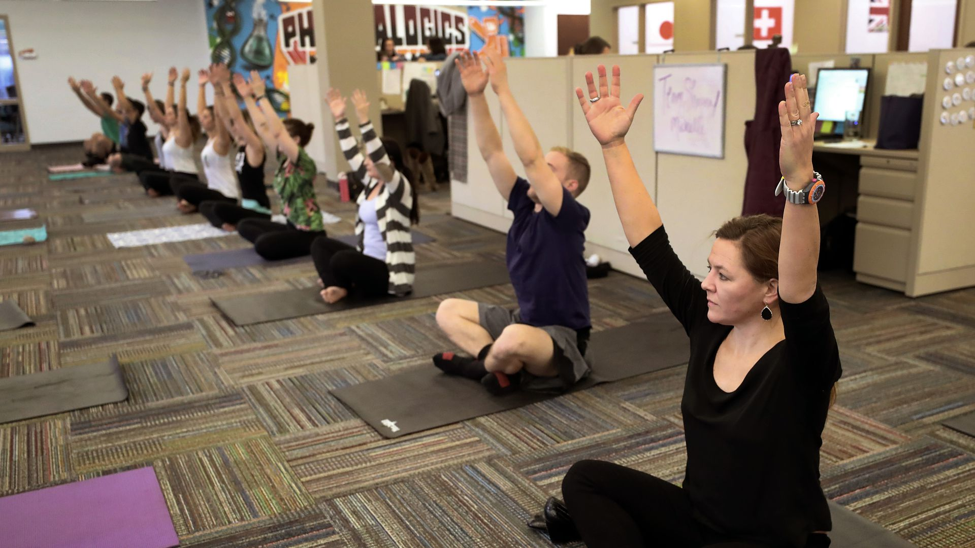 Employees practice yoga in the office.