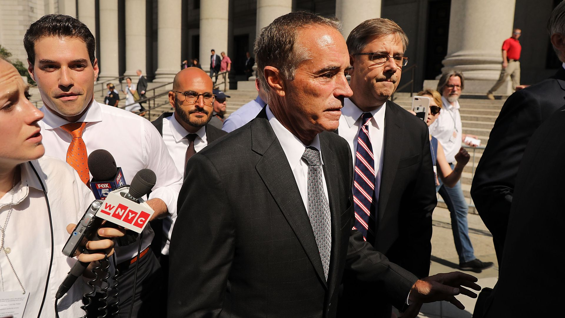 Chris collins outside of the DC courthouse in a black suit surrounded by reporters during the day.