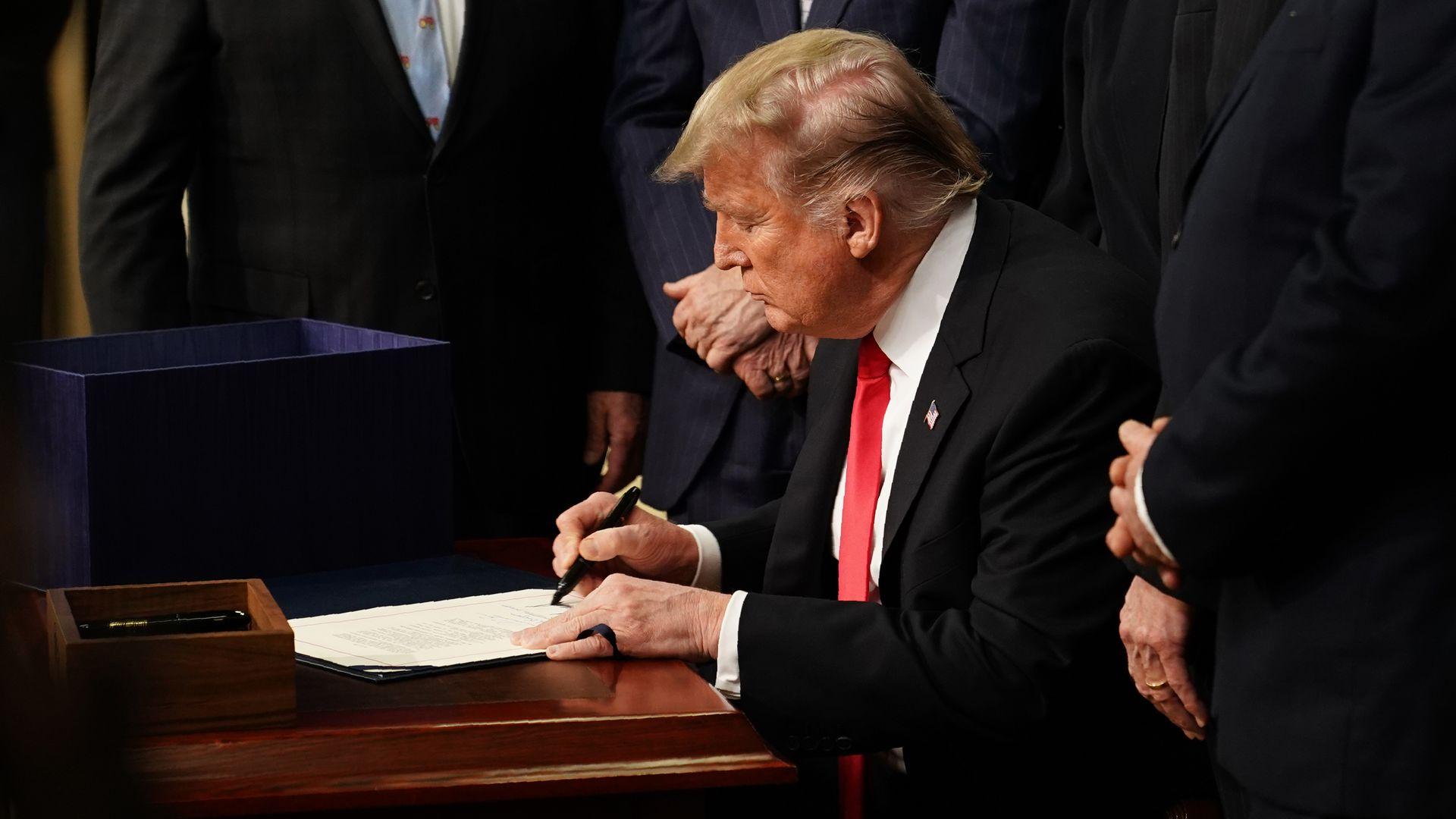 Donald Trump signing a bill.