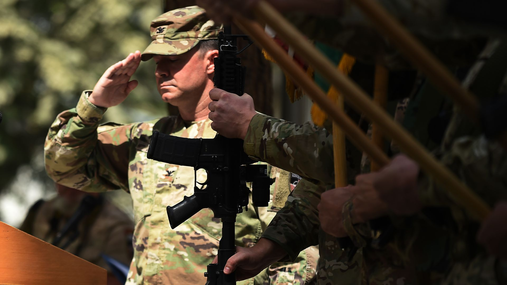 U.S. soldier salutes, behind a silhouette of a gun.