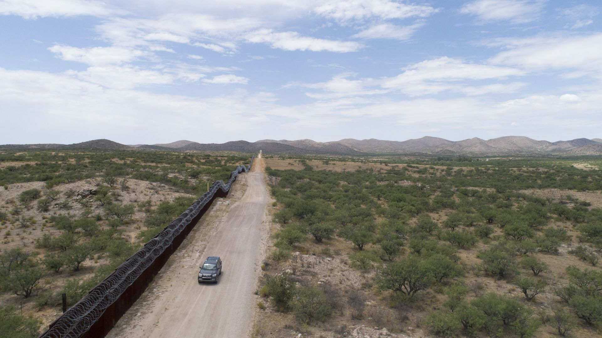 A car driving along a dirt road by a border fence on the southwest border.
