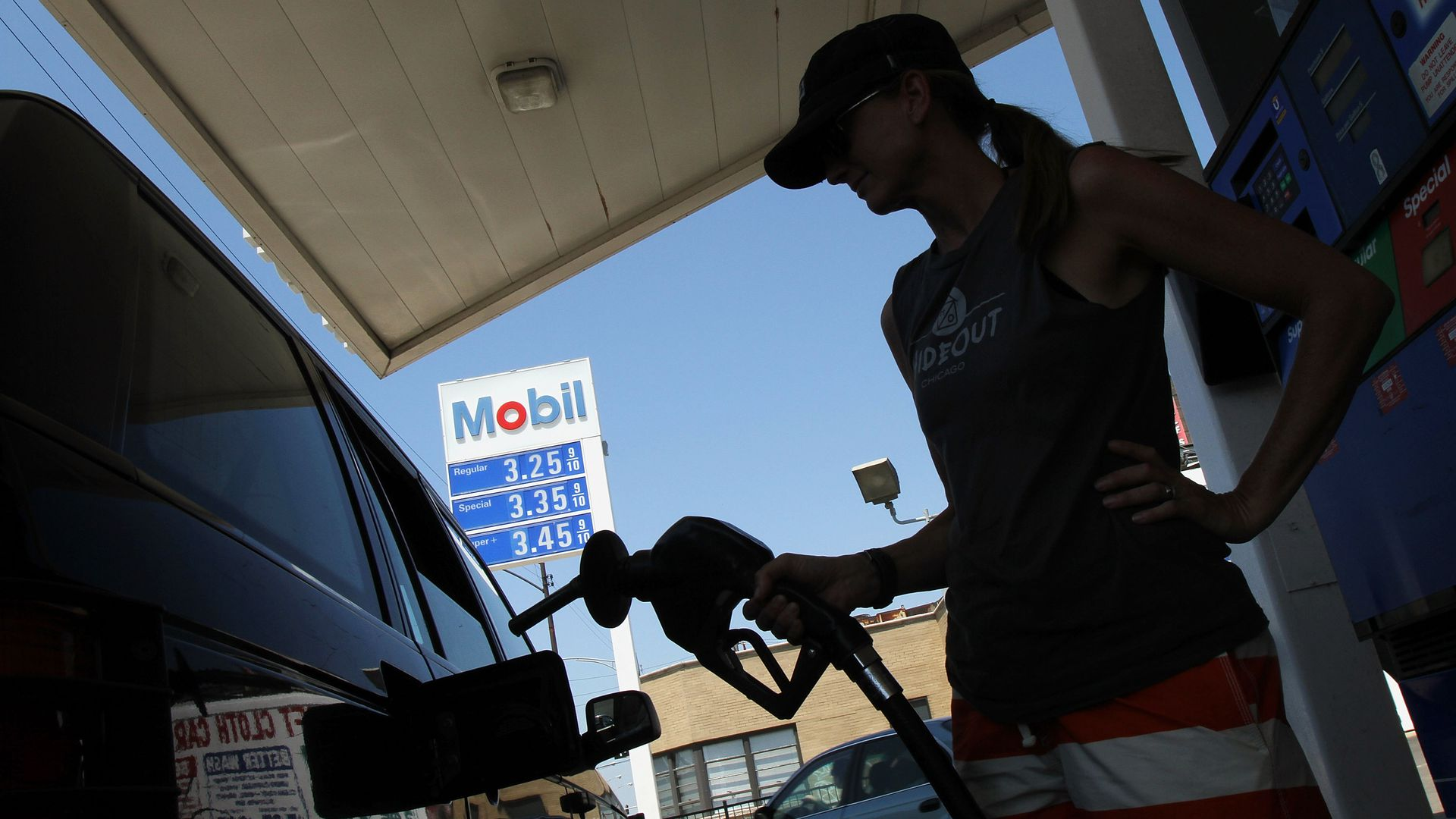 A woman filling up her car at an Exxon station.