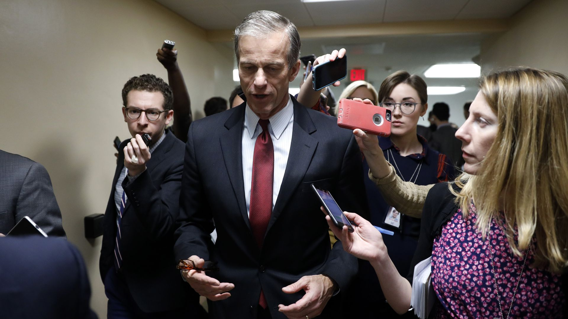 Senator John Thune walks in a suit as reporters follow him asking questions