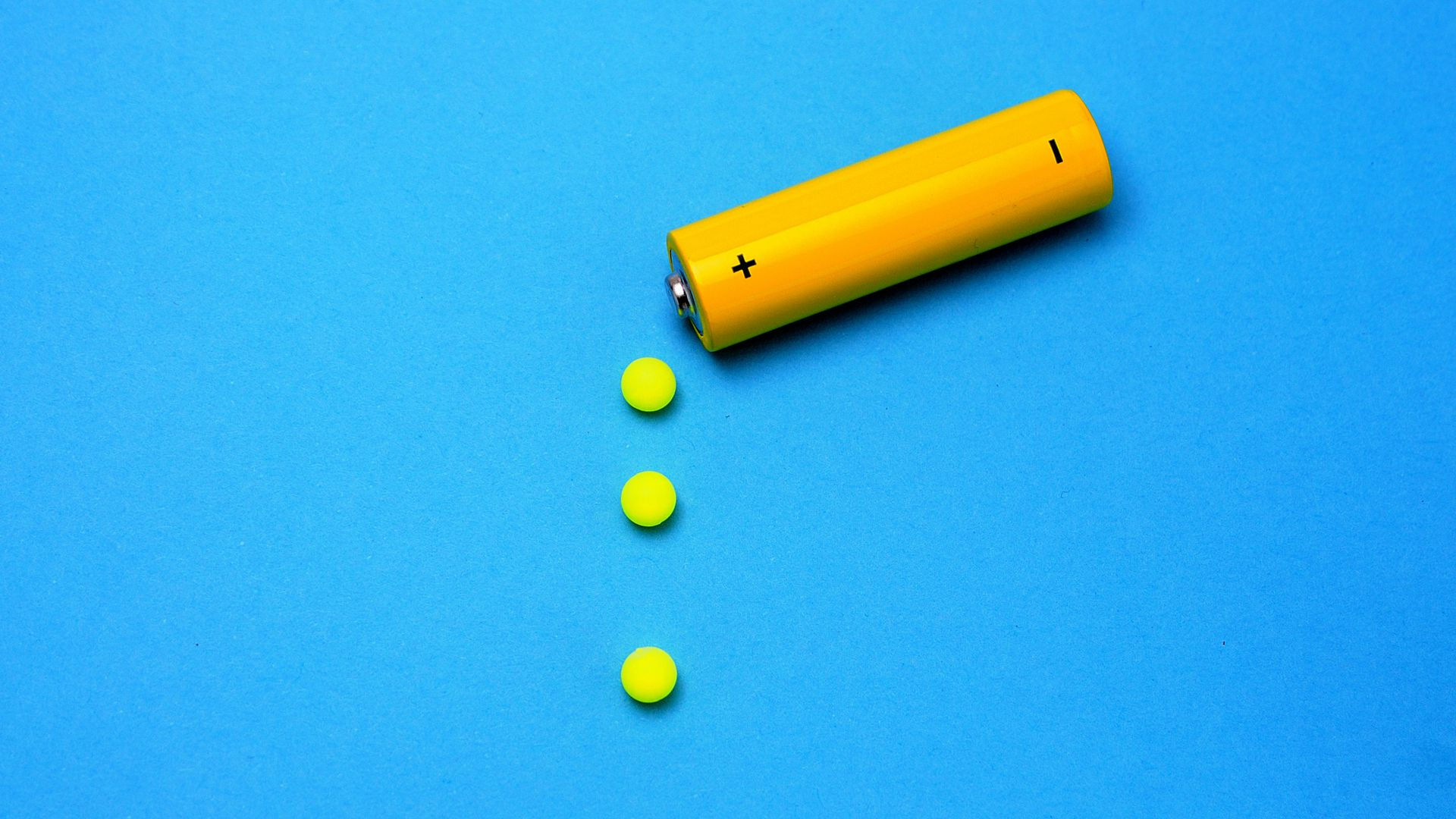 In this image, a yellow battery drips yellow circles on top of a blue background.
