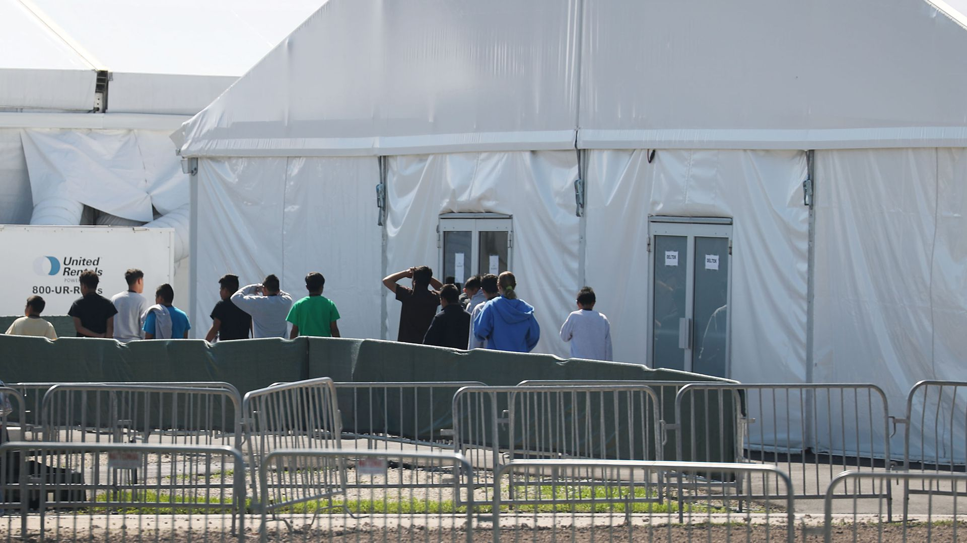 Children walk in a line out of a large white tent with double doors at the Homestead facility.
