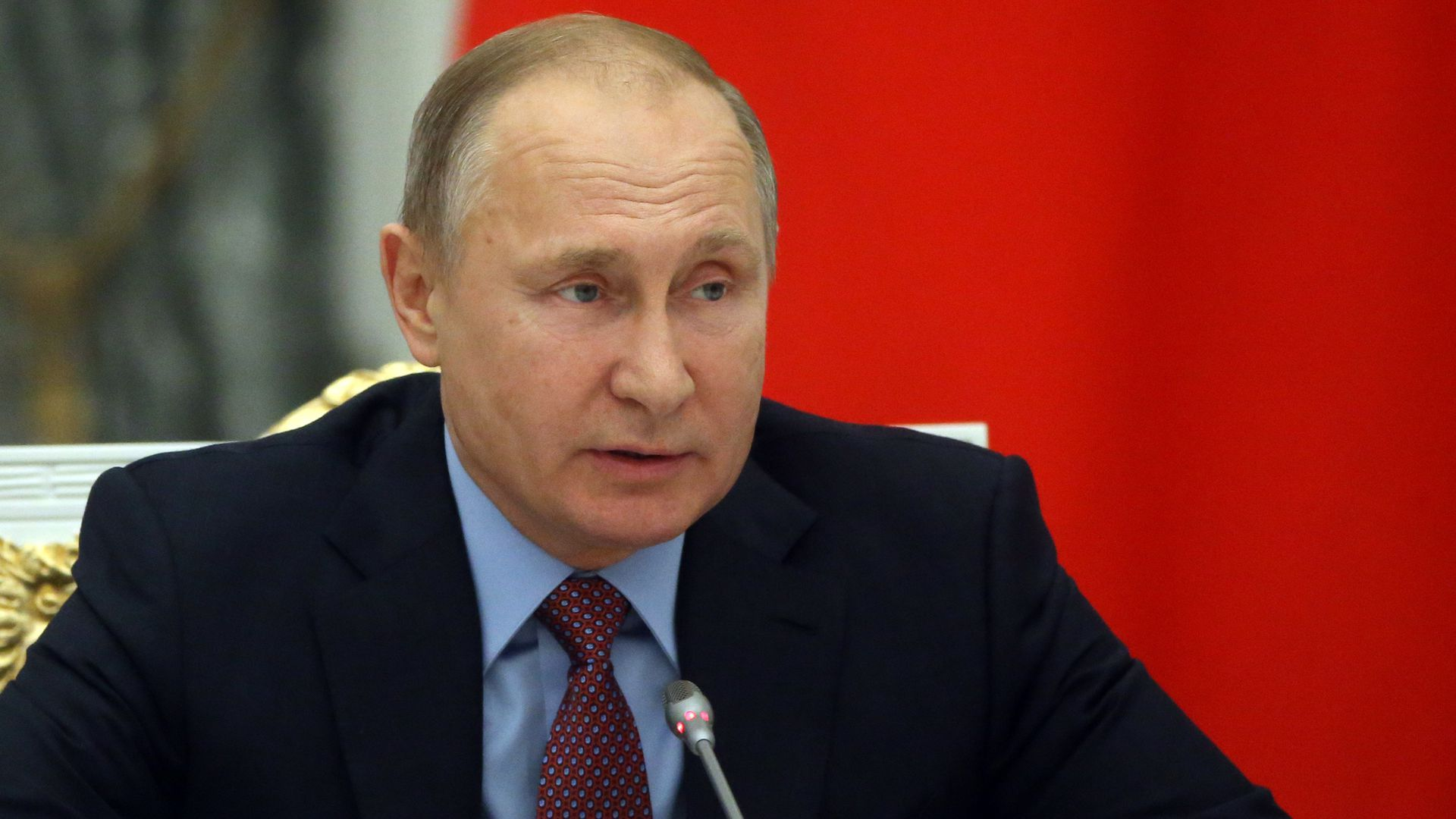Vladimir Putin seated at microphone during meeting