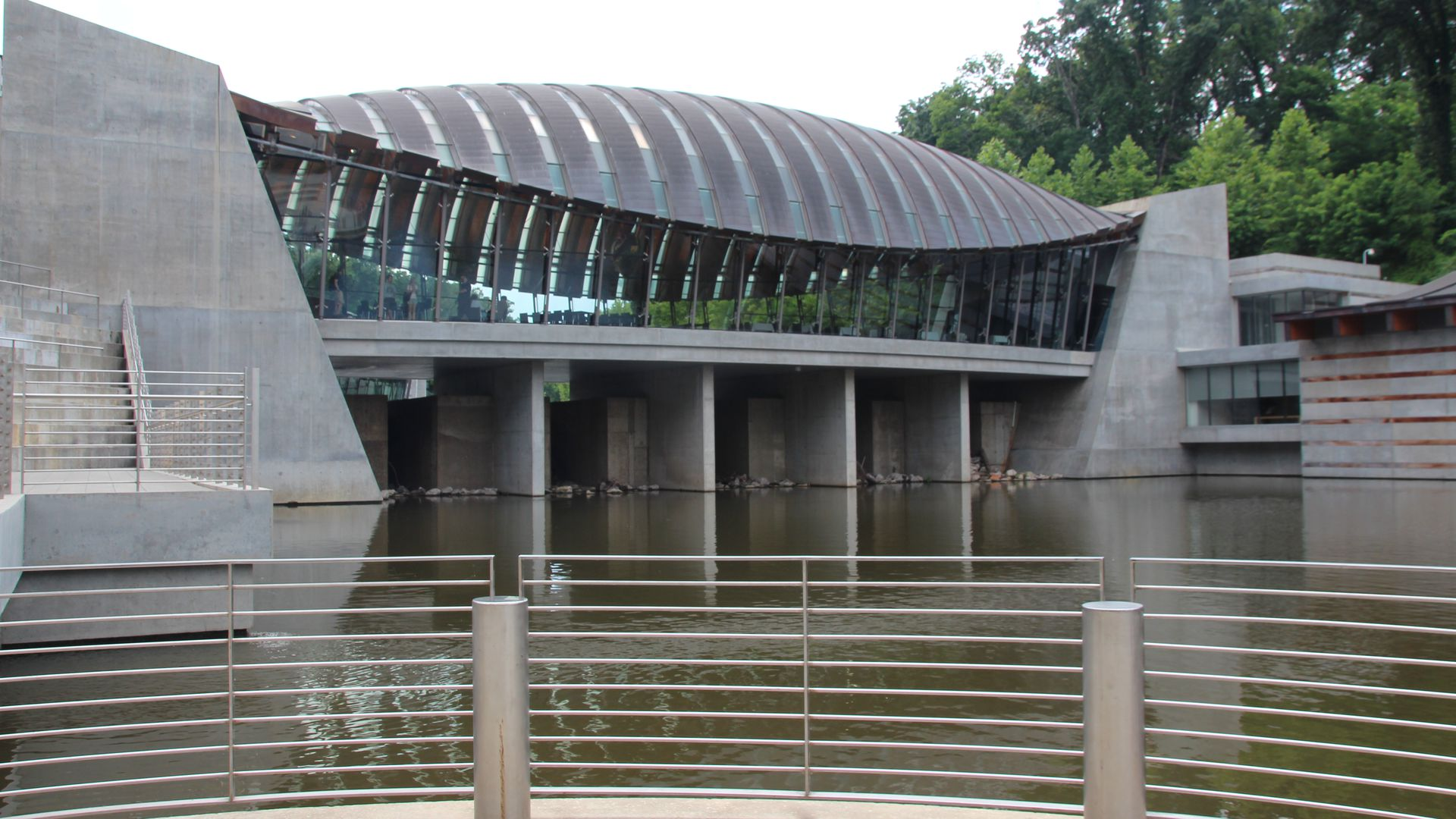 A view of the outside of the Crystal Bridges art museum, surrounded by a body of water.