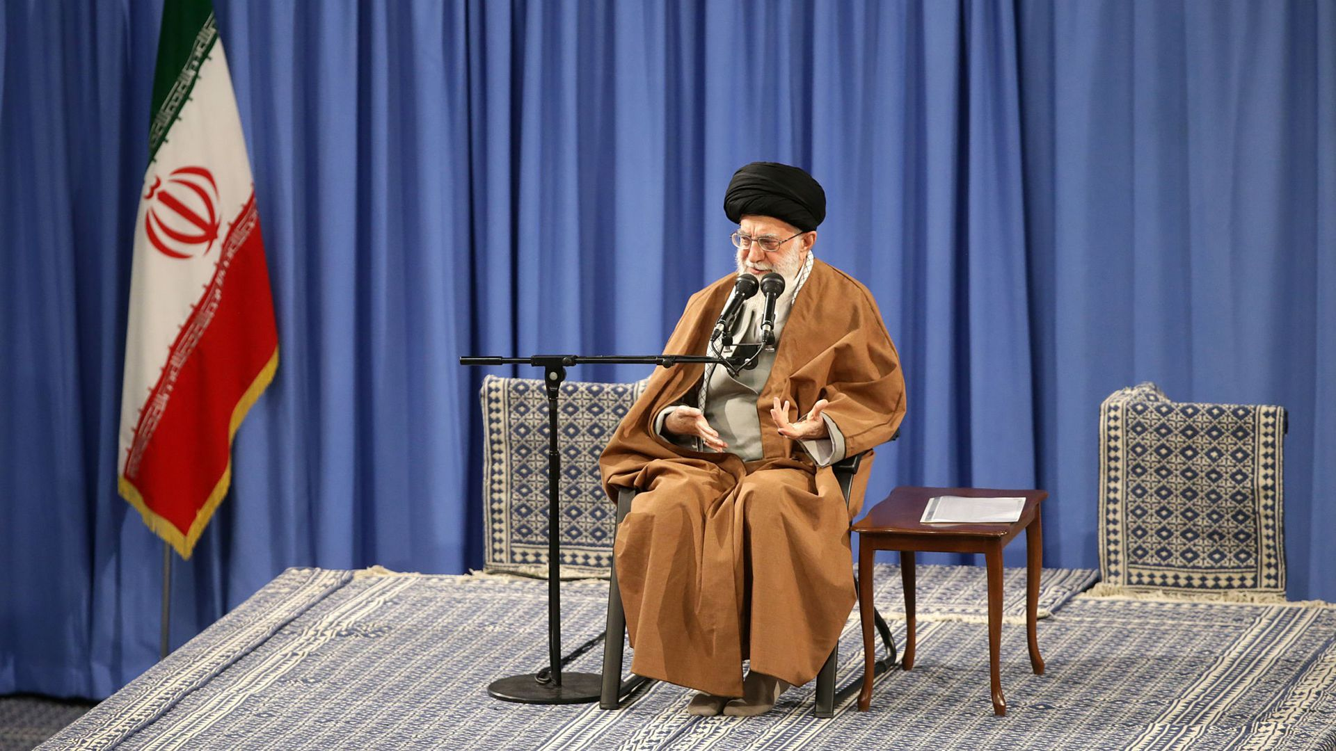 Khamenei seated in a chair on stage, next to the Iranian flag