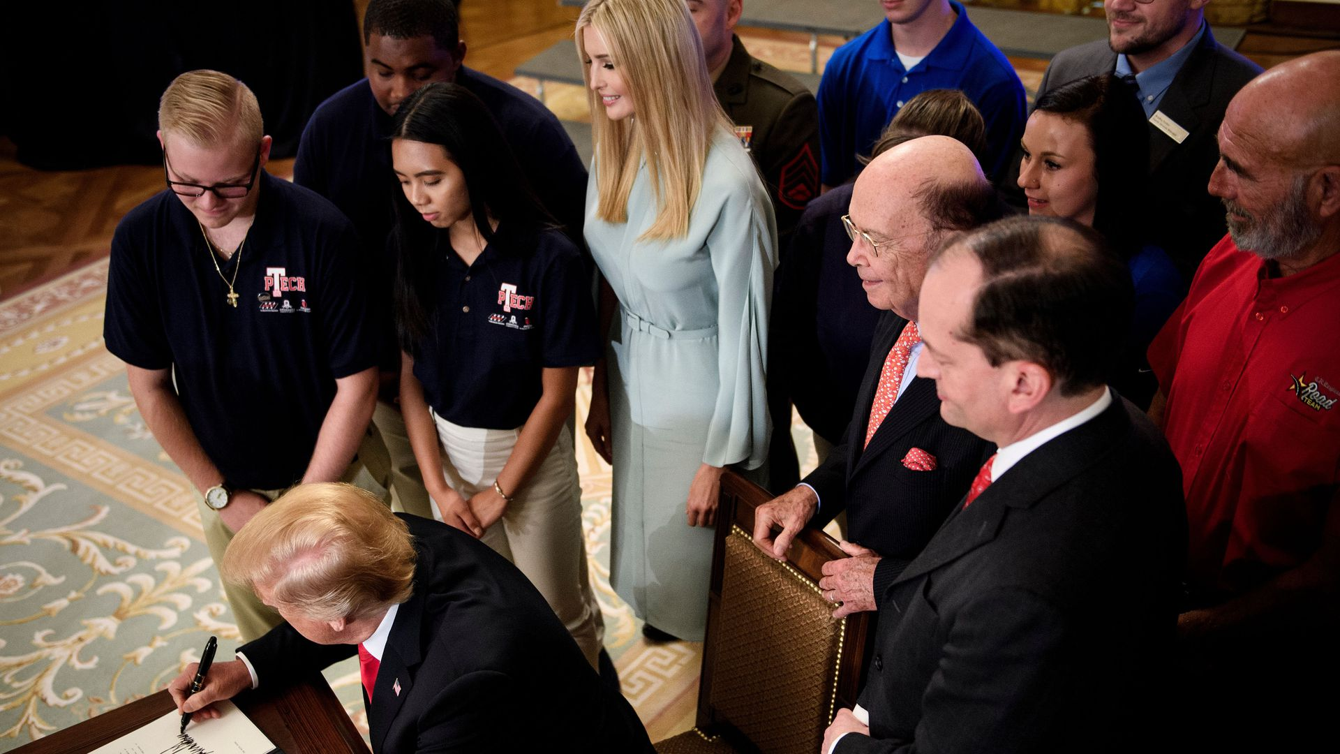 Donald Trump surrounded by Ivanka Trump and guests signing executive order on worker training