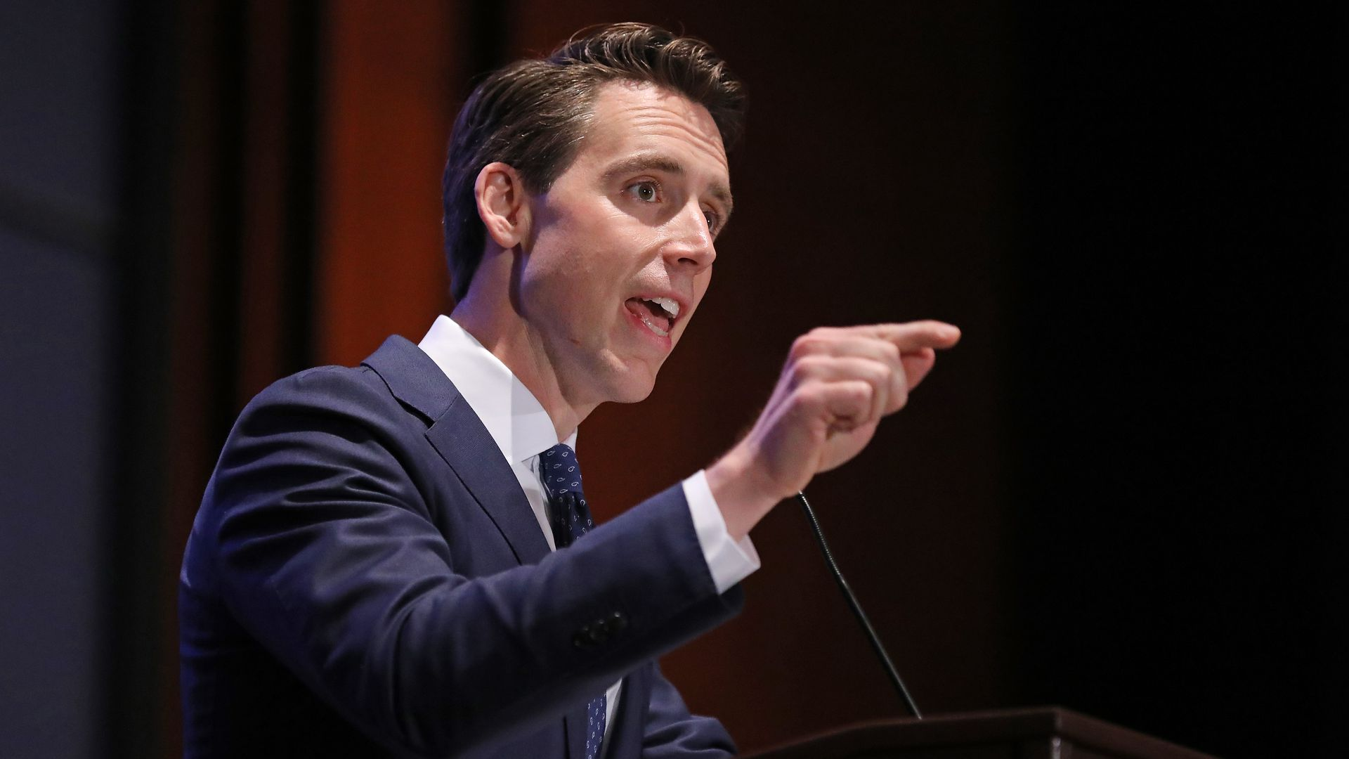 A photo of Sen. Josh Hawley standing and pointing at a microphone.