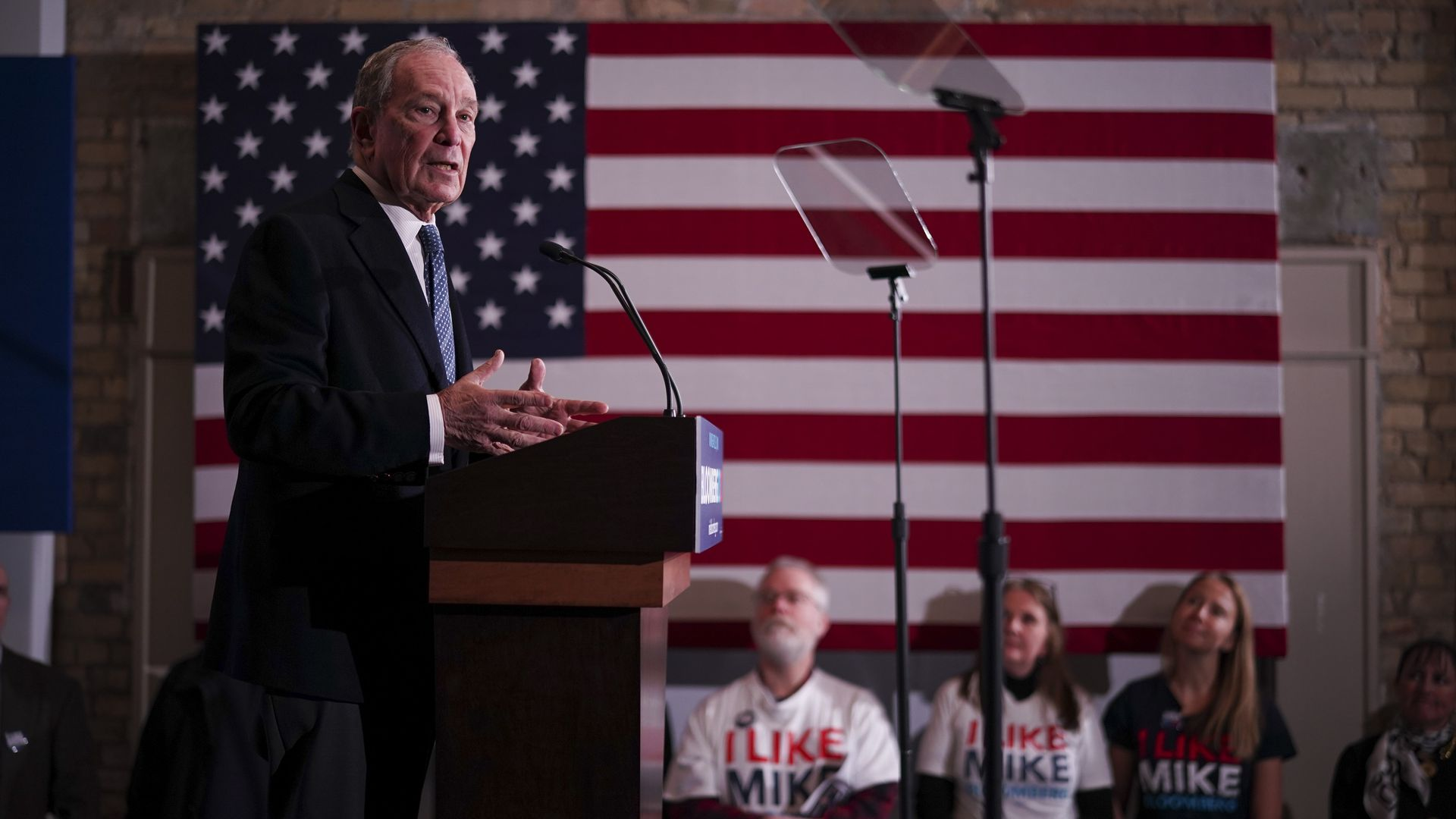 In this image, Mike Bloomberg stands in front of an American flag while on the 2020 campaign trail