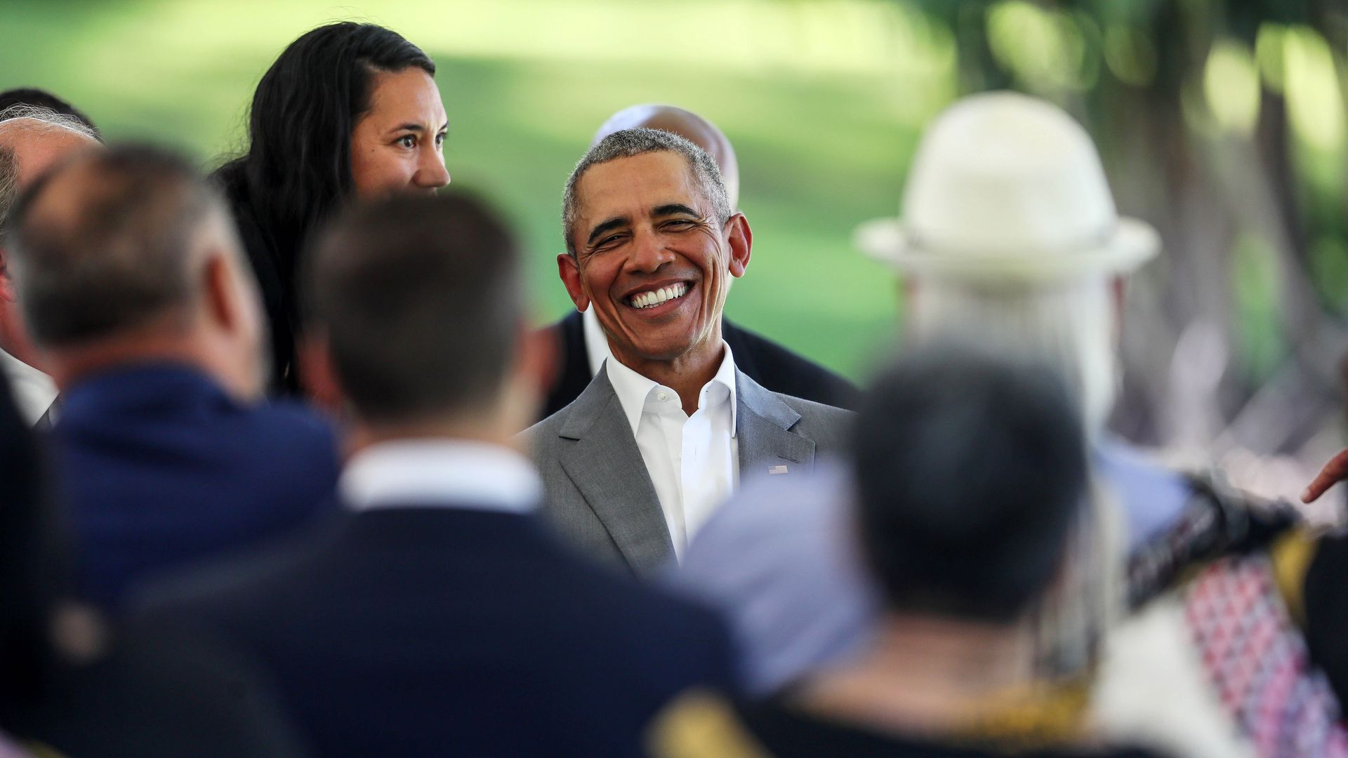 Former president Barack Obama smiling in a crowd.