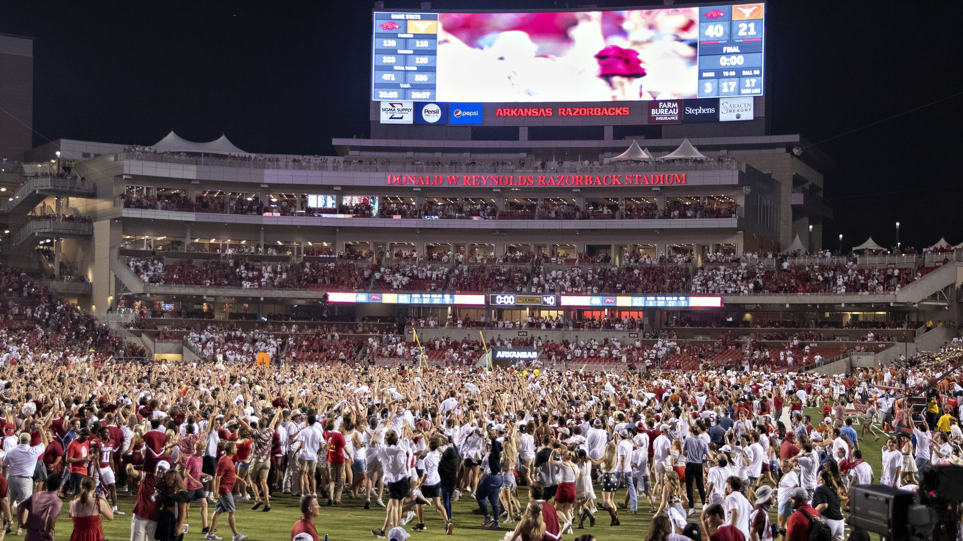 A crowd of people on the football field after the Razorbacks-Longhorns game.