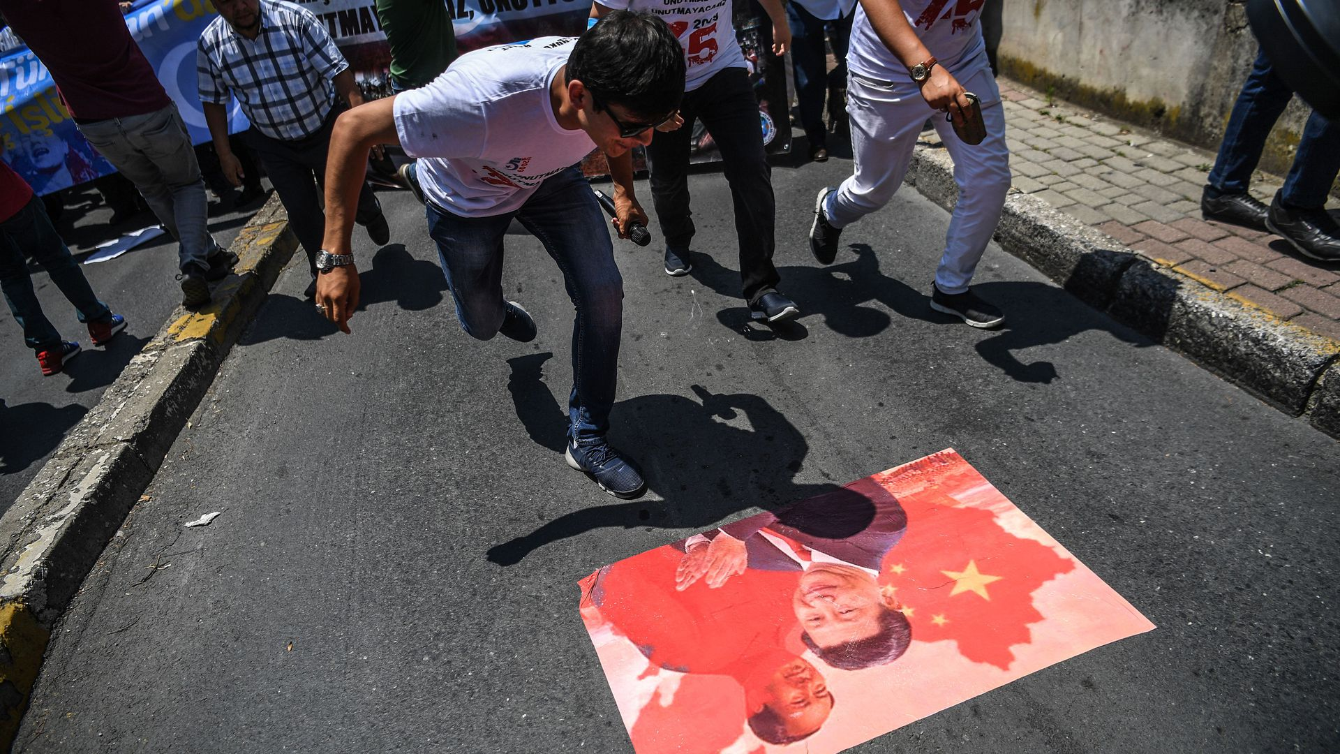 People spit on a poster of Chinese President Xi Jinping.