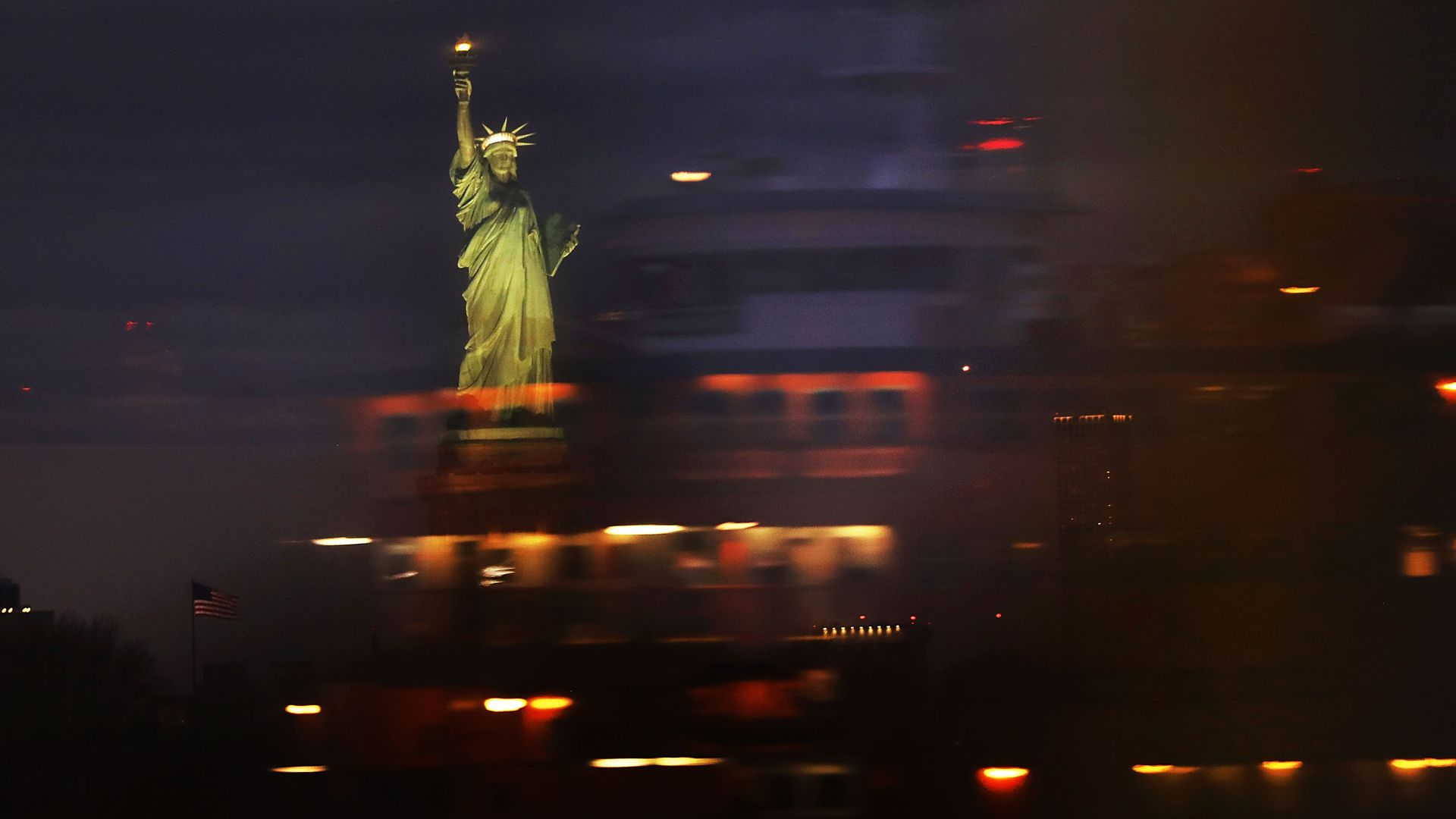 The Statue of Liberty seen through a blur of moving cars and lights