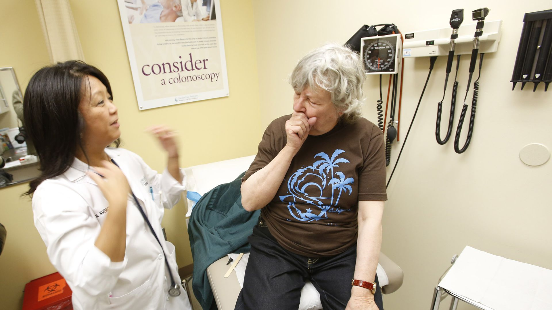 A patient sits on an exam table and coughs while a physician looks at her.