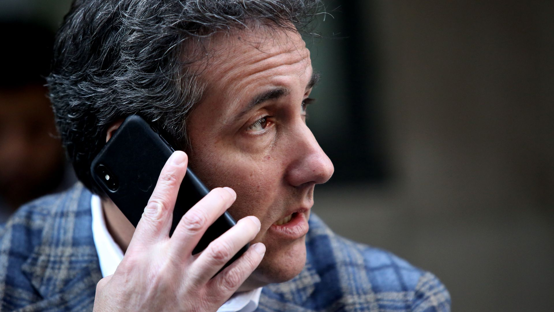 Michael Cohen holding a phone to his ear.