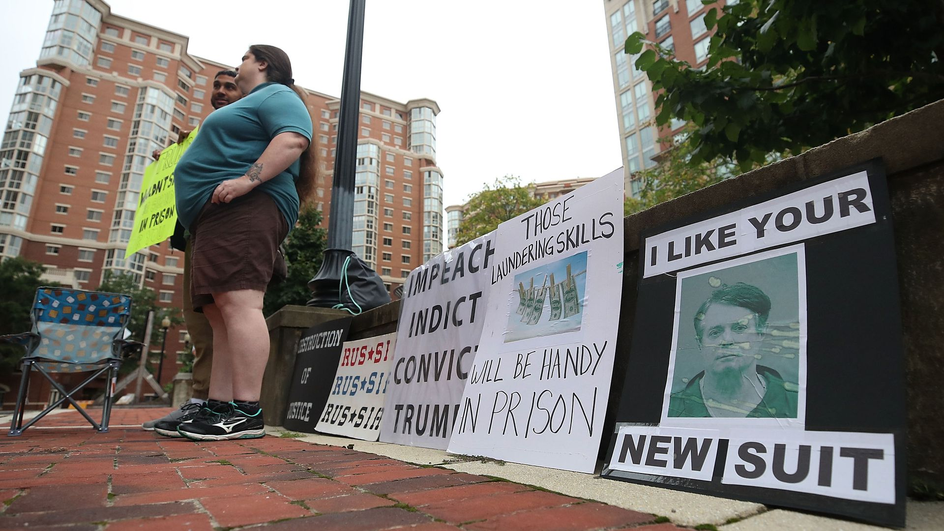 """A sign next to protestors with a mugshot of Paul Manafort, that reads """"I like your new suit."""""""