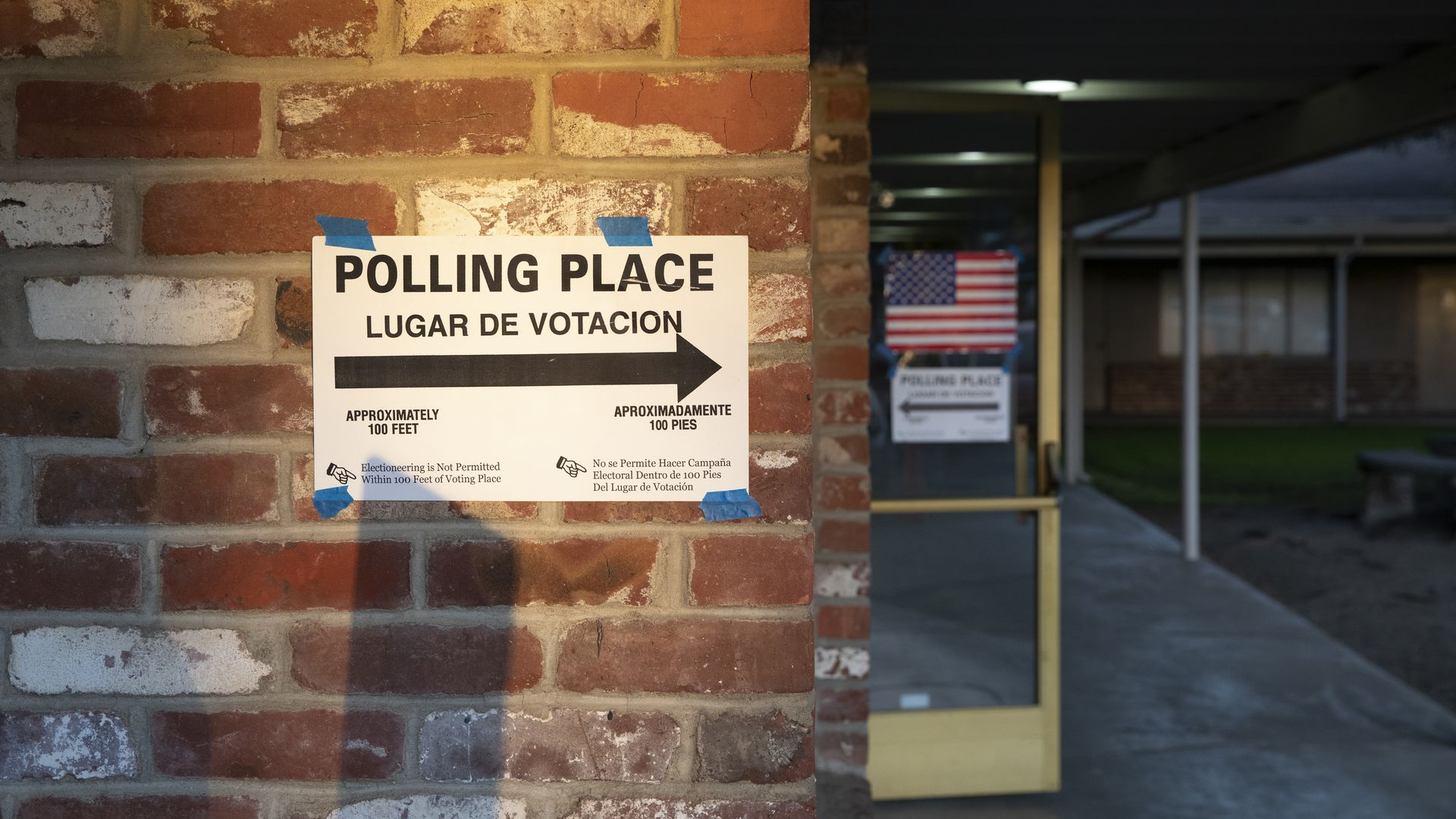 A sigh for a polling place on a brick wall