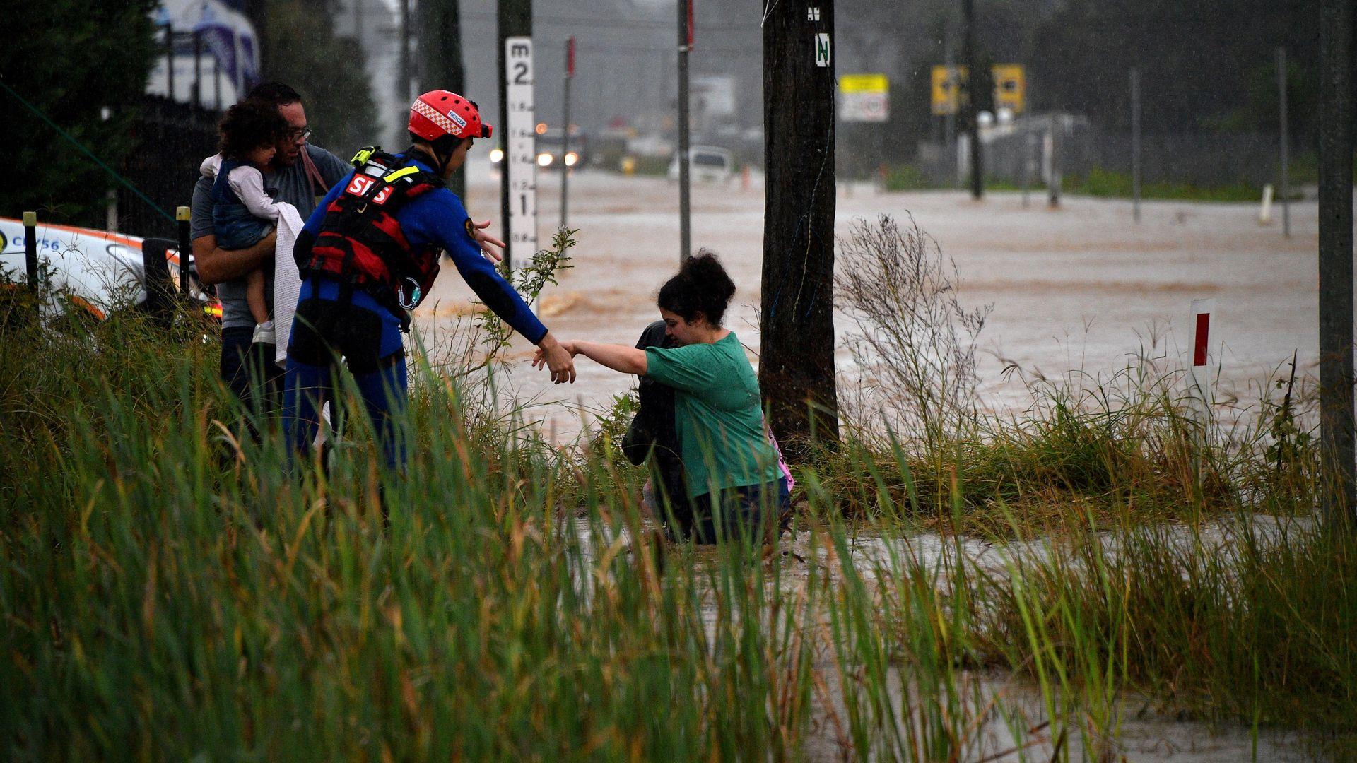 Ein Rettungsarbeiter hilft den Bewohnern am 20. März bei starkem Regen im Westen Sydneys, eine überflutete Straße zu überqueren