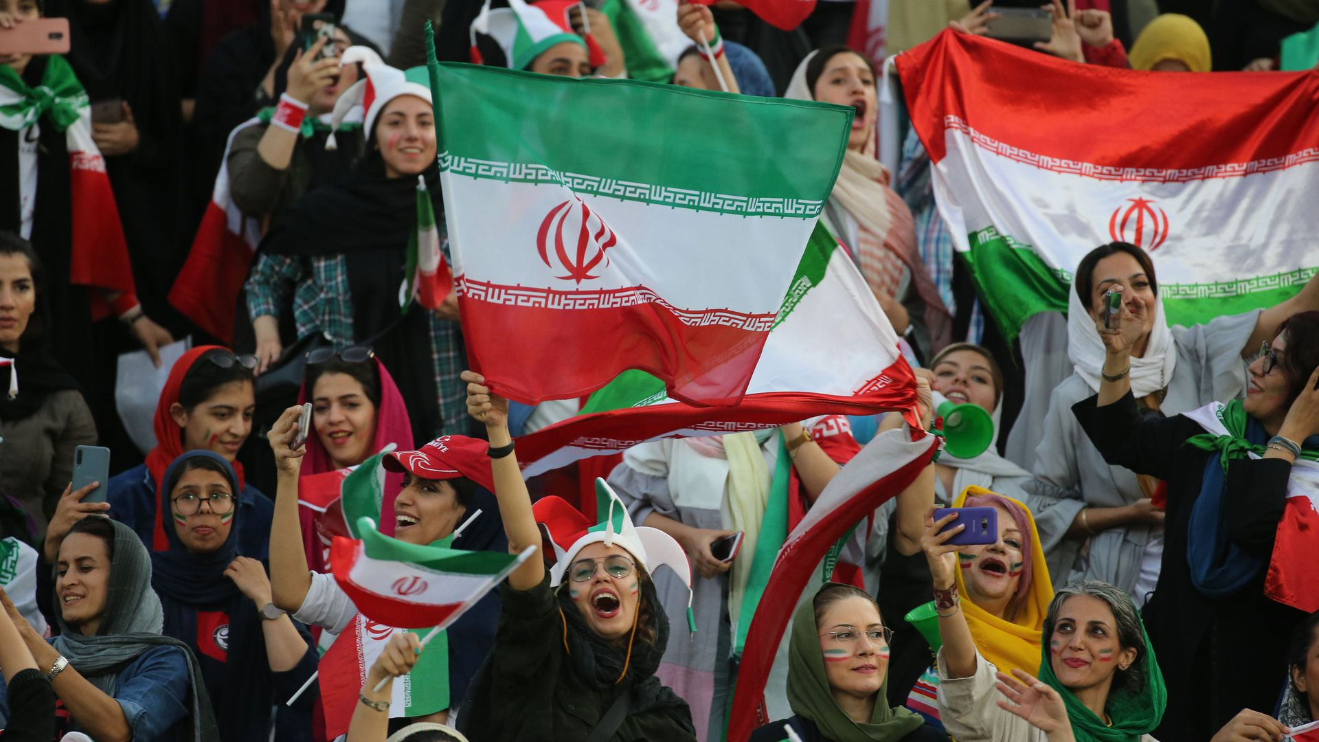 Iranian women cheering at a soccer game