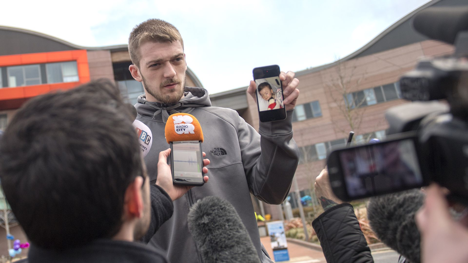 Tom Evans, Father of Alfie Evans, holds a photograph of his son as he speaks to media outside Alder Hey Children's Hospital.