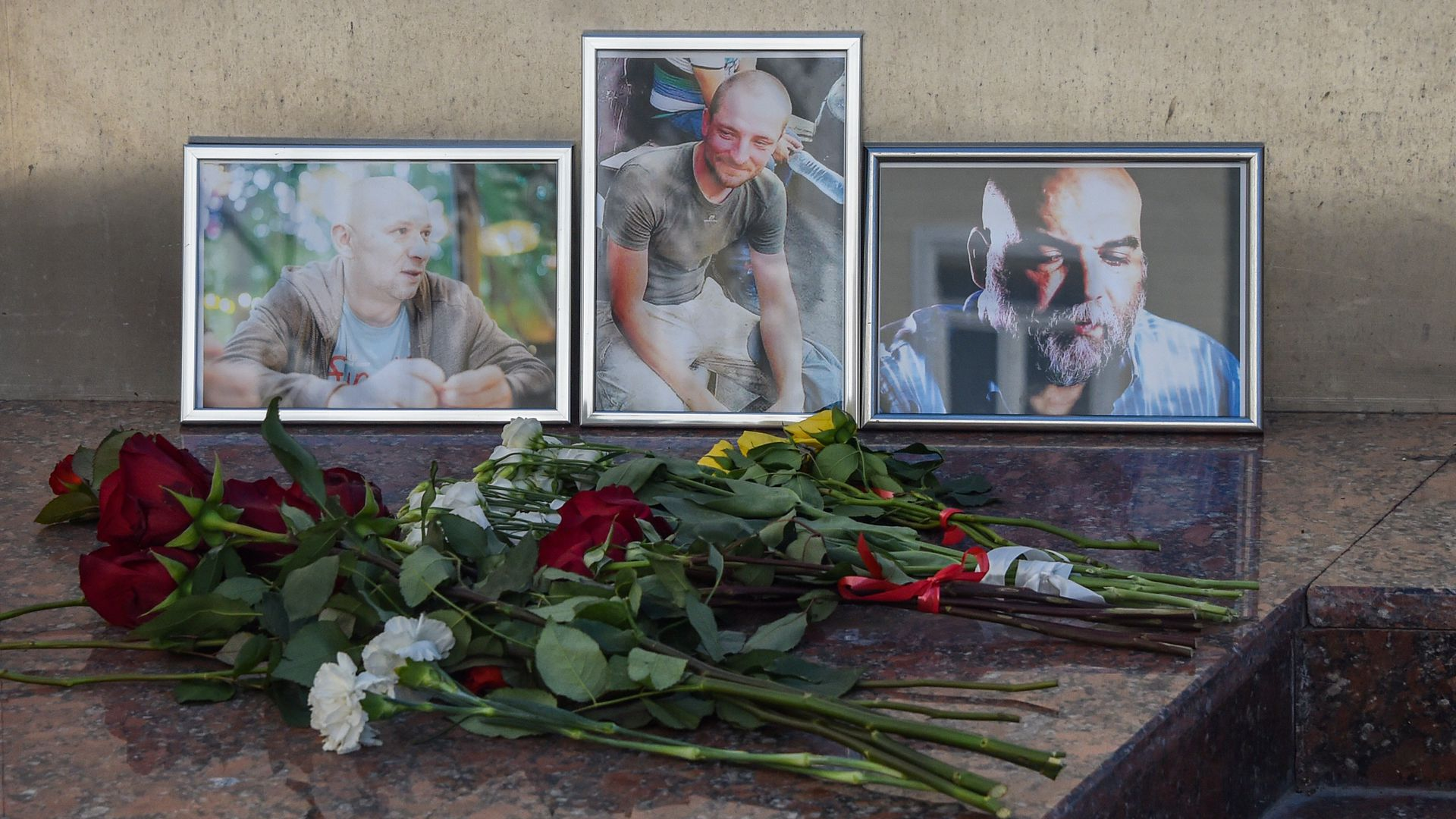 Flowers left in front of photos of three Russian journalists