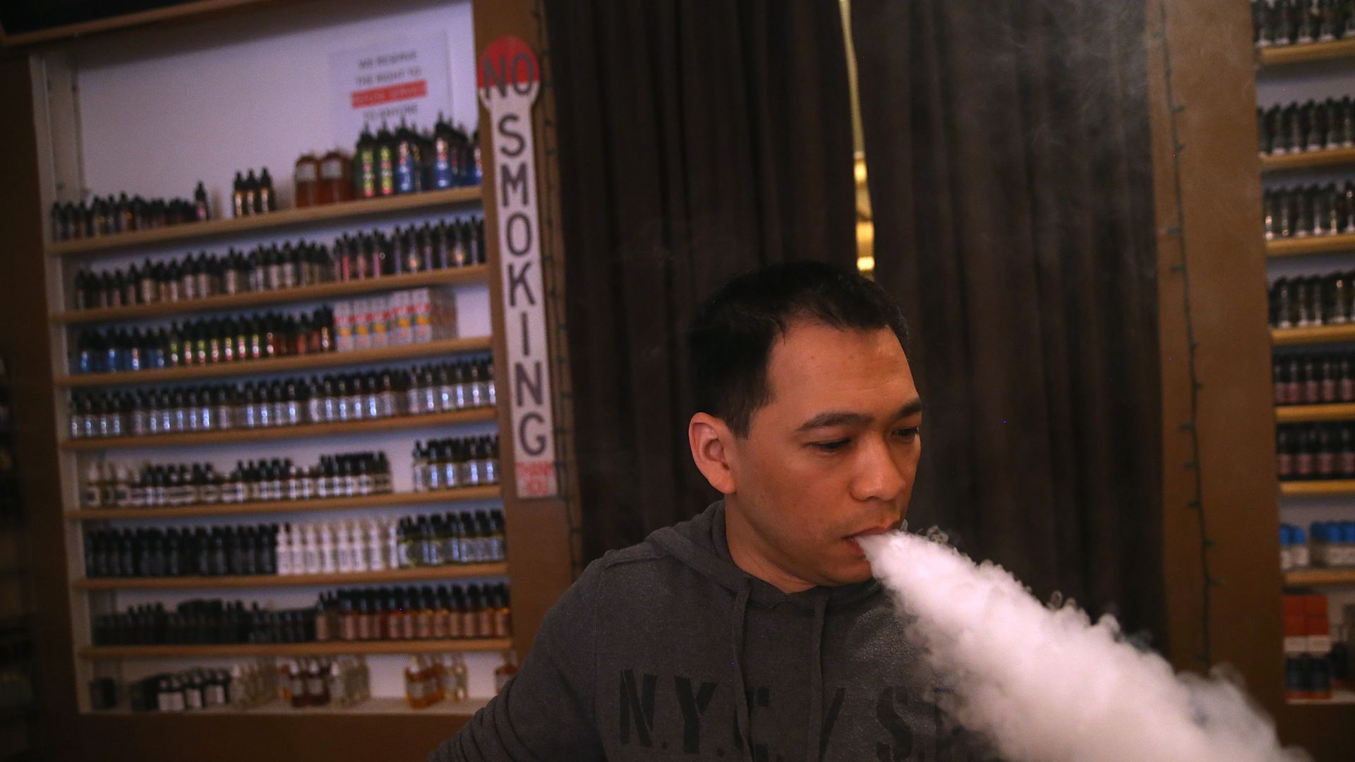 "In this image, a man blows a cloud of white smoke down and behind him a shelf of vaping products says ""no smoking."""