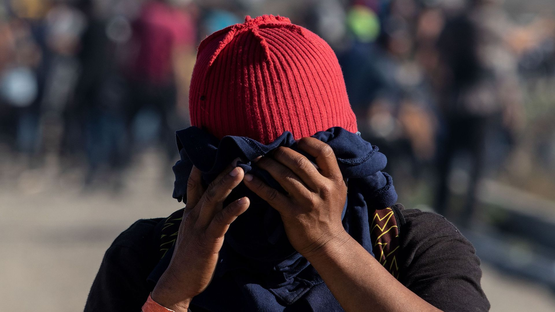 A close up shot of a migrant wearing a red hat and using a navy blue t-shirt to cover their face as tear gas is launched from U.S. border agents.