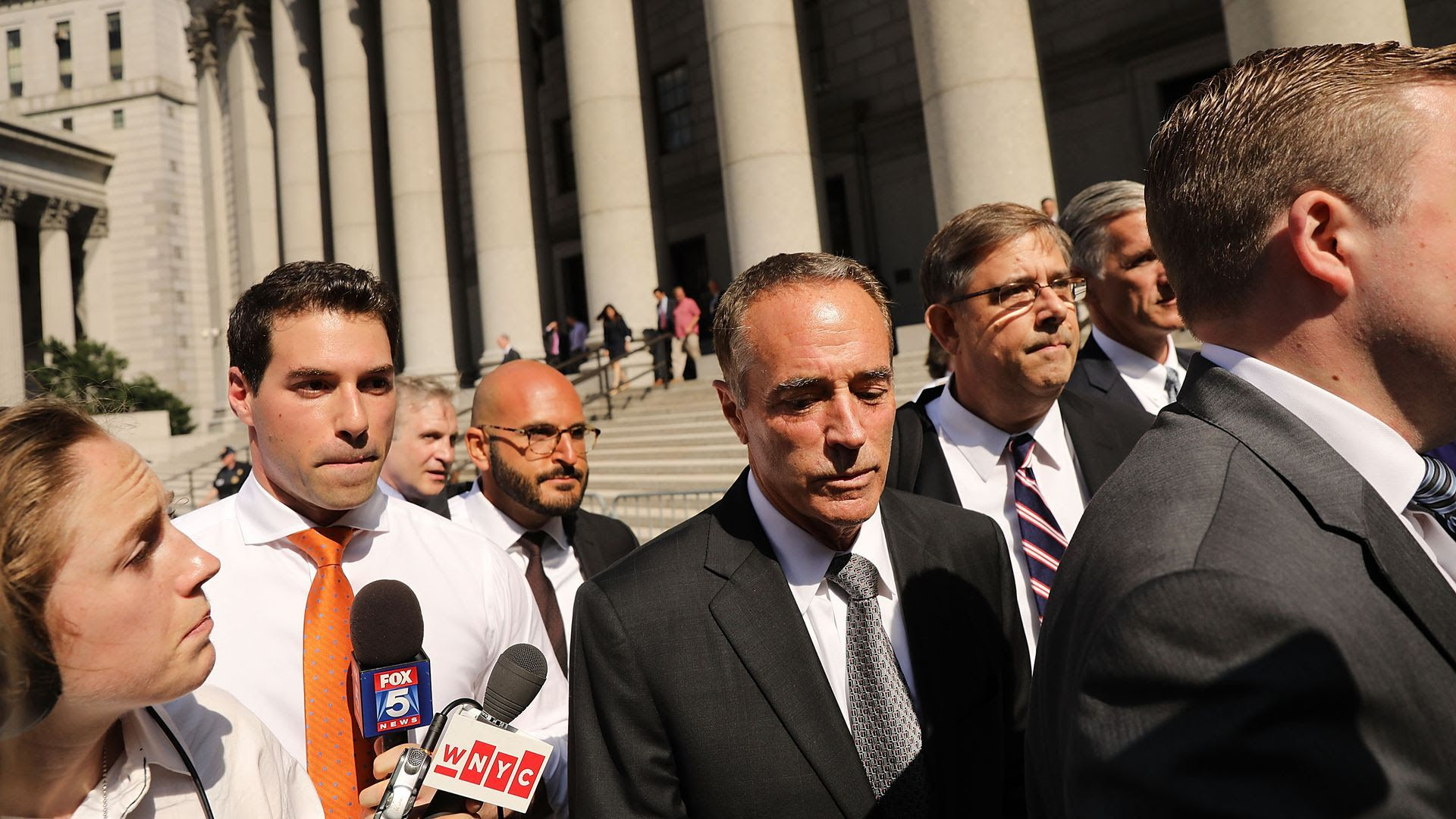 Chris Collins walks out of court with media holding microphones near him.