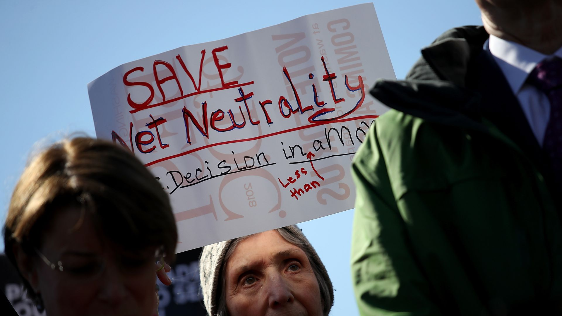 "A woman holds a sign that says ""Save net neutrality"""