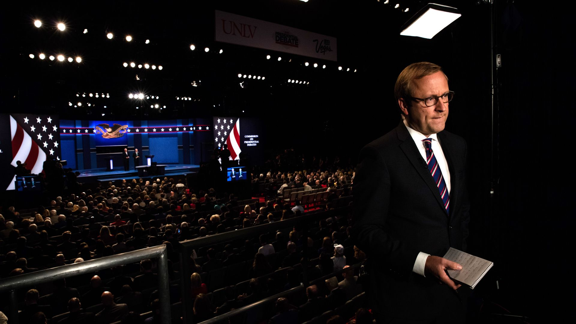 In this image, Jonathan Karl stands and holds a book with a debate stage and crowd behind him.